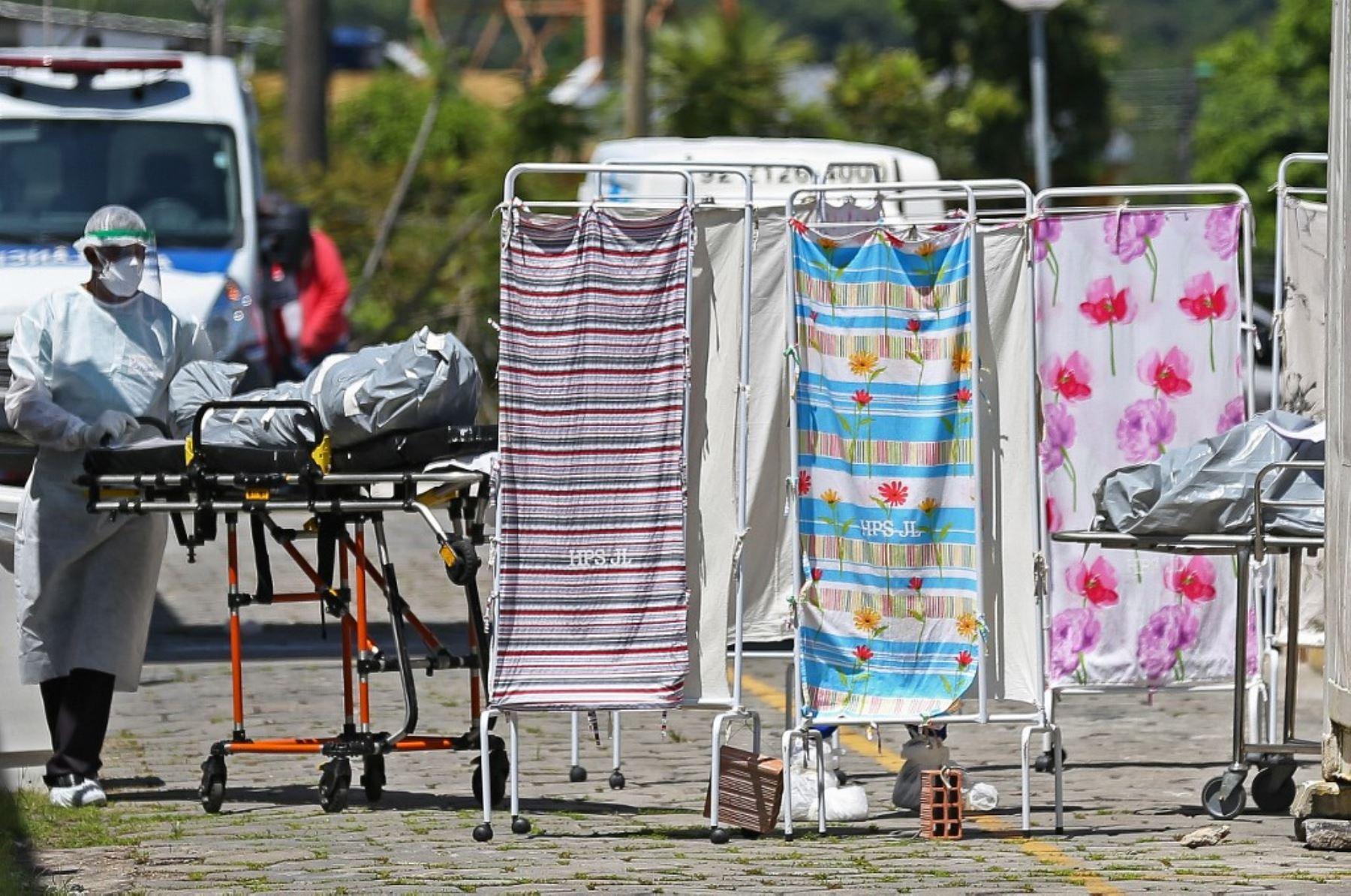 Cadáveres de las víctimas del coronavirus covid-19 son trasladados por un miembro del personal médico con traje protector a un área refrigerada del Hospital Joao Lucio en Manaus, estado de Amazonas, Brasil. Foto: AFP