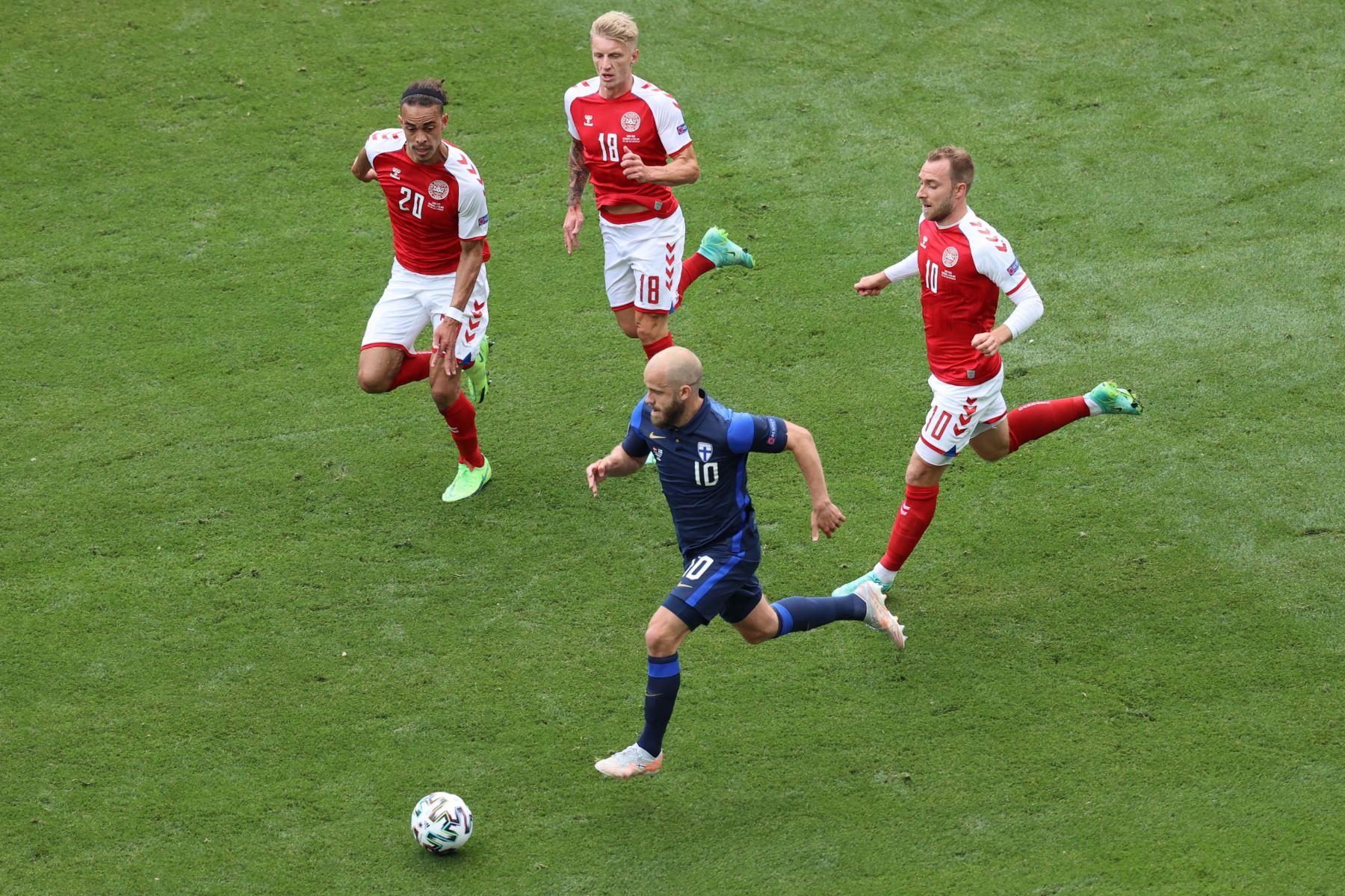 El delantero de Finlandia Teemu Pukki corre con el balón pasando (atrás LR) El delantero de Dinamarca Yussuf Poulsen, el defensor de Dinamarca Daniel Wass y el mediocampista de Dinamarca Christian Eriksen durante el partido de fútbol del Grupo B de la UEFA EURO 2020 entre Dinamarca y Finlandia. Foto: AFP