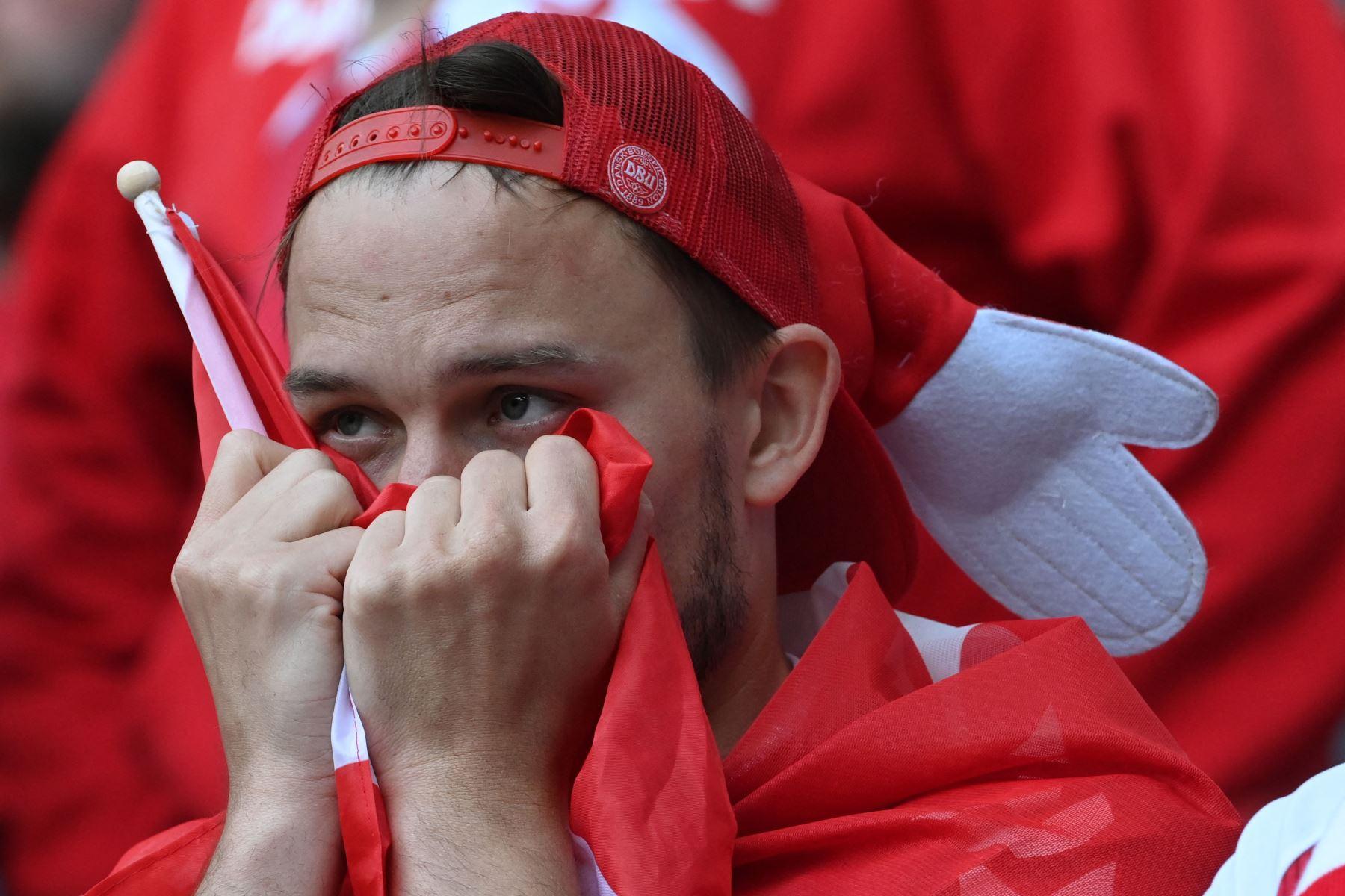 Los aficionados reaccionan entre la multitud después de que el mediocampista danés Christian Eriksen se derrumbara en el campo durante el partido de fútbol del Grupo B de la UEFA EURO 2020 entre Dinamarca y Finlandia. Foto: AFP