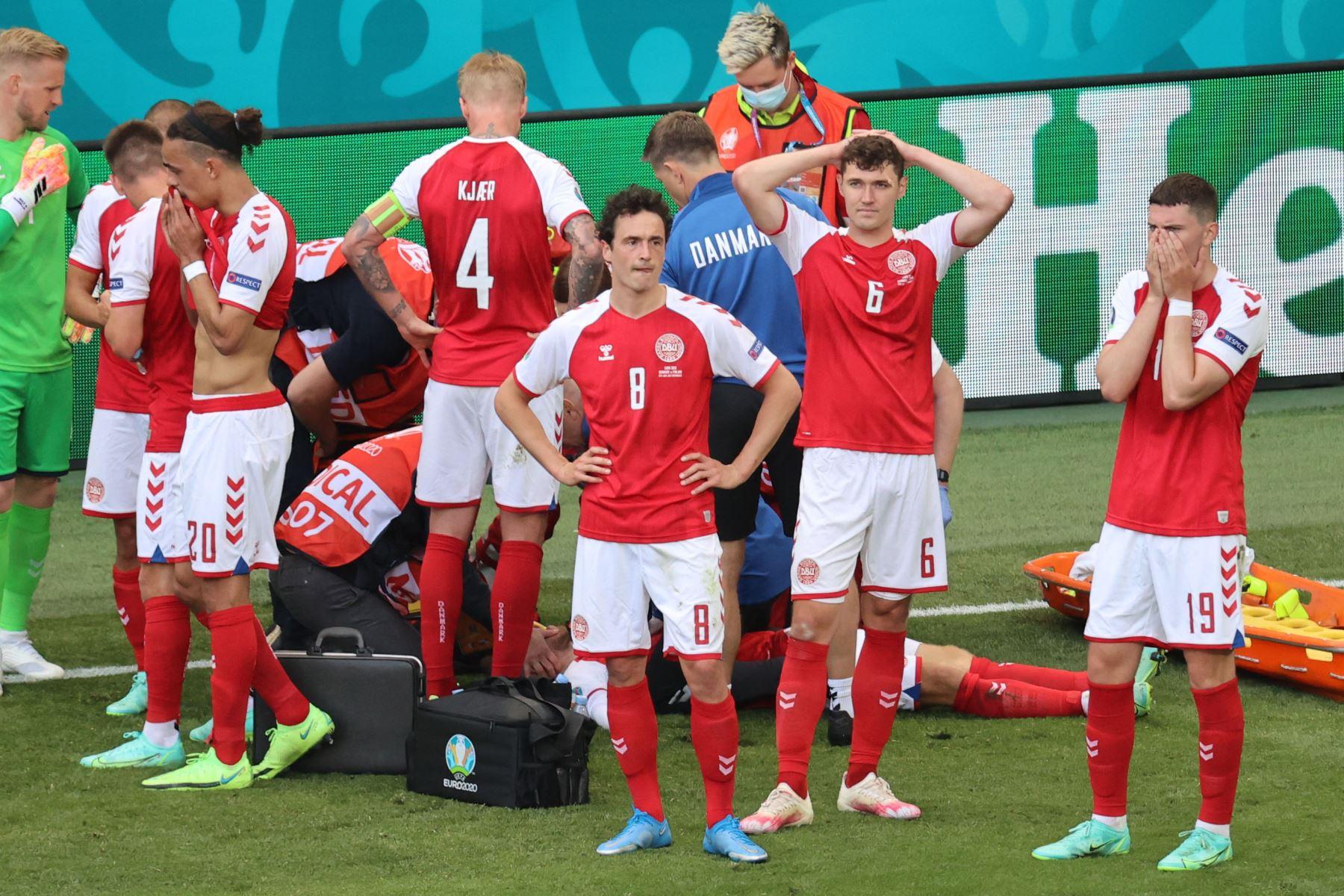 Los jugadores de Dinamarca reaccionan cuando los paramédicos atienden al mediocampista danés Christian Eriksen después de que se derrumbó en el campo durante el partido de fútbol del Grupo B de la UEFA EURO 2020 entre Dinamarca y Finlandia. Foto: AFP