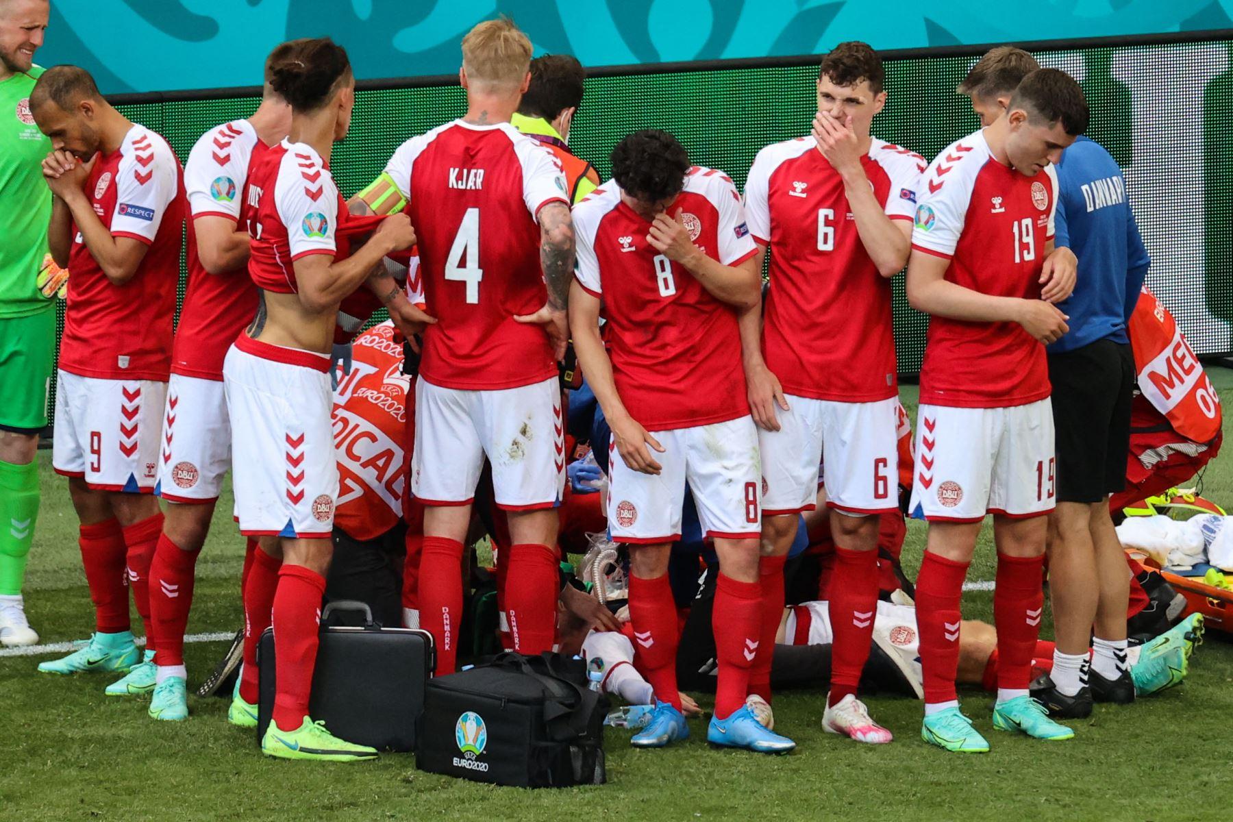 Los jugadores de Dinamarca se reúnen mientras los paramédicos atienden al mediocampista Christian Eriksen durante el partido de fútbol del Grupo B de la UEFA EURO 2020 entre Dinamarca y Finlandia en el Estadio Parken en Copenhague. Foto: AFP