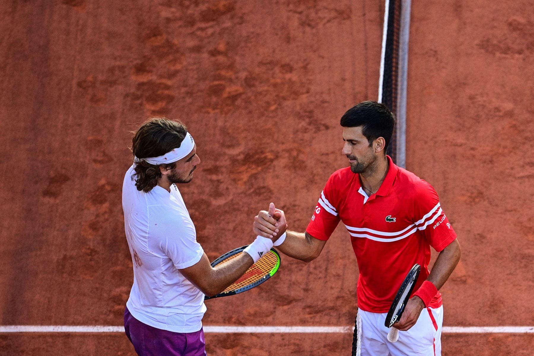El serbio Novak Djokovic  y el griego Stefanos Tsitsipas se dan la mano al final de su último partido de tenis masculino en el día 15 del torneo de tenis Roland Garros 2021 del Abierto de Francia en París. Foto: AFP