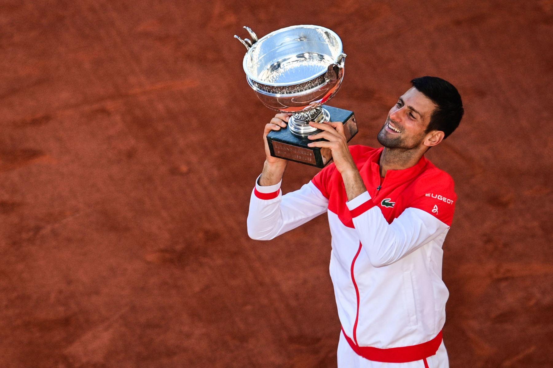 El serbio Novak Djokovic posa con la Copa Mousquetaires (Los Mosqueteros) después de vencer al griego Stefanos Tsitsipas al final de su último partido de tenis masculino el día 15 del torneo de tenis Roland Garros 2021 del Abierto de Francia en París. Foto: AFP