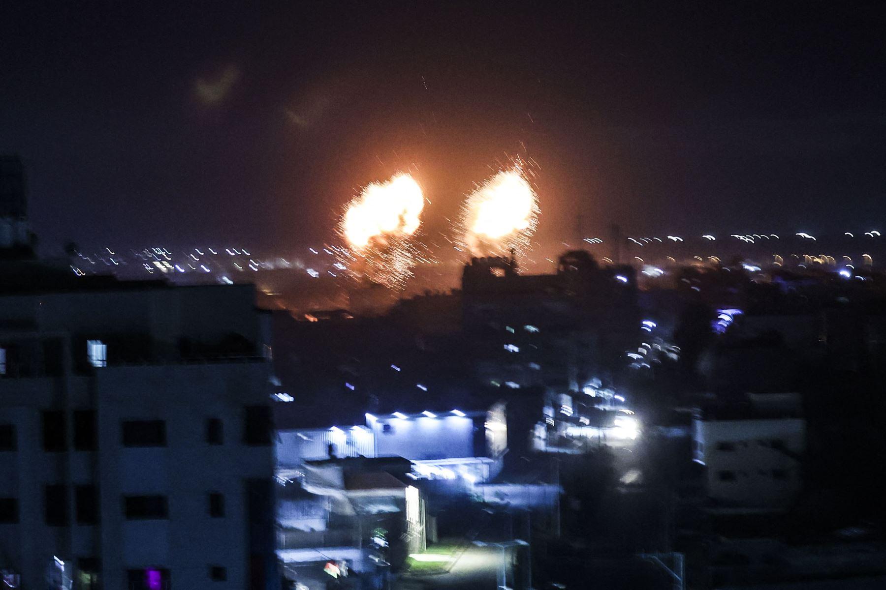 Las explosiones iluminan el cielo sobre los edificios en Gaza, mientras las fuerzas israelíes bombardean el enclave palestino. Foto: AFP.