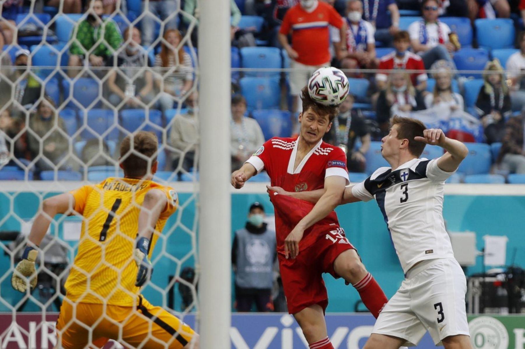 El delantero ruso Aleksey Miranchuk (C) cabecea el balón junto al defensor de Finlandia Daniel O