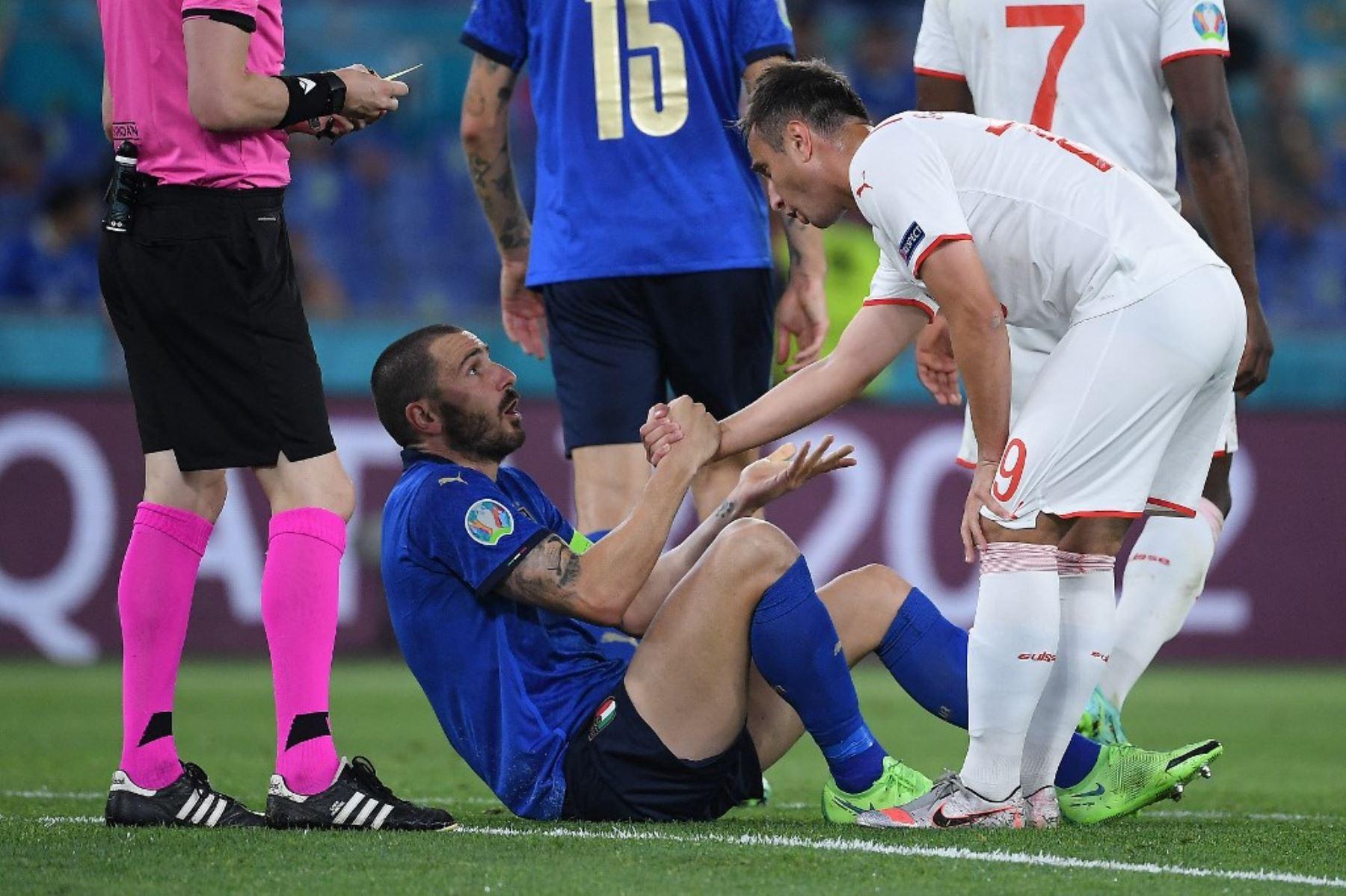 El defensa italiano Leonardo Bonucci (C) es ayudado a ponerse de pie por el delantero suizo Mario Gavranovic (R) durante el partido de fútbol del Grupo A de la UEFA EURO 2020 entre Italia y Suiza en el Estadio Olímpico de Roma el 16 de junio de 2021. Foto: AFP