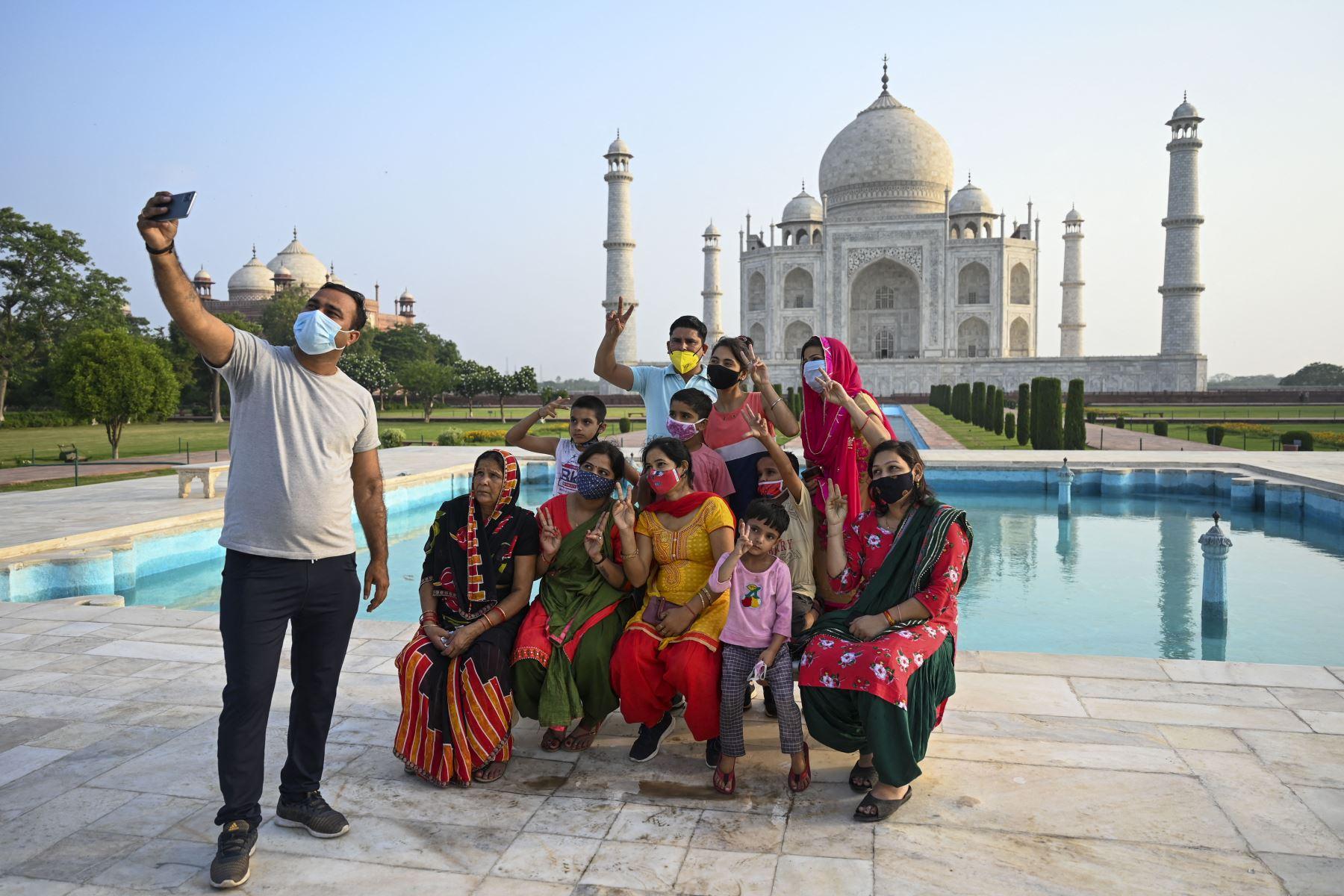 Un grupo de turistas toma fotos de recuerdo en el Taj Mahal después de que reabrió a los visitantes luego de que las autoridades flexibilizaran las restricciones del covid-19 en Agra. Foto: AFP