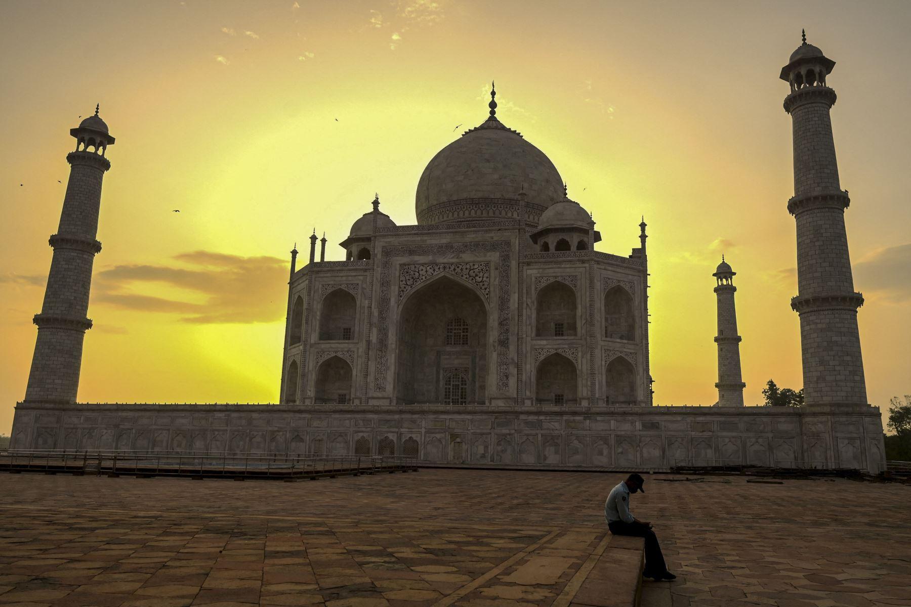 Un guardia de seguridad se toma un descanso cuando sale el sol detrás del Taj Mahal después de que reabriera a los visitantes luego de que las autoridades suavizaran las restricciones del coronavirus  en Agra. Foto: AFP