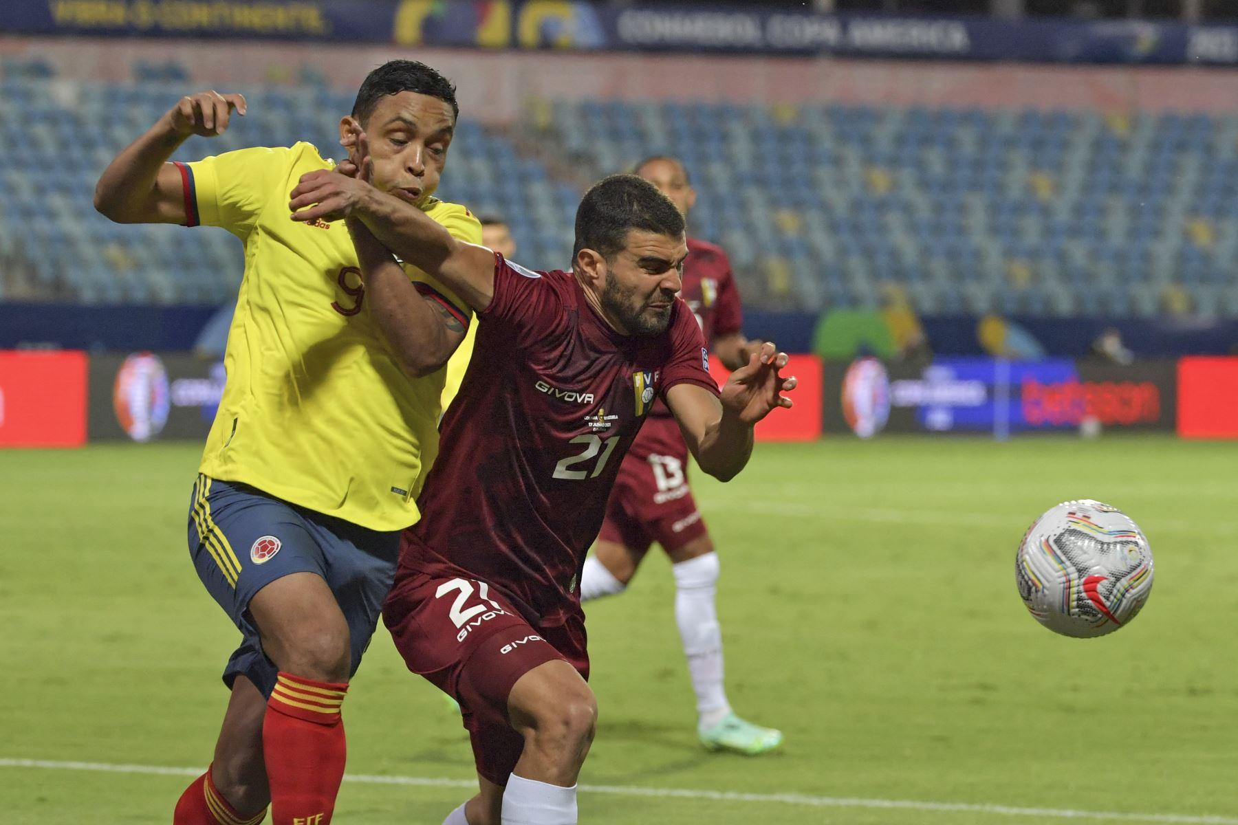 El colombiano Luis Muriel y el venezolano Alexander González compiten por el balón durante el partido de la fase de grupos de la Copa América, en el Estadio Olímpico de Goiania, Brasil. Foto: AFP