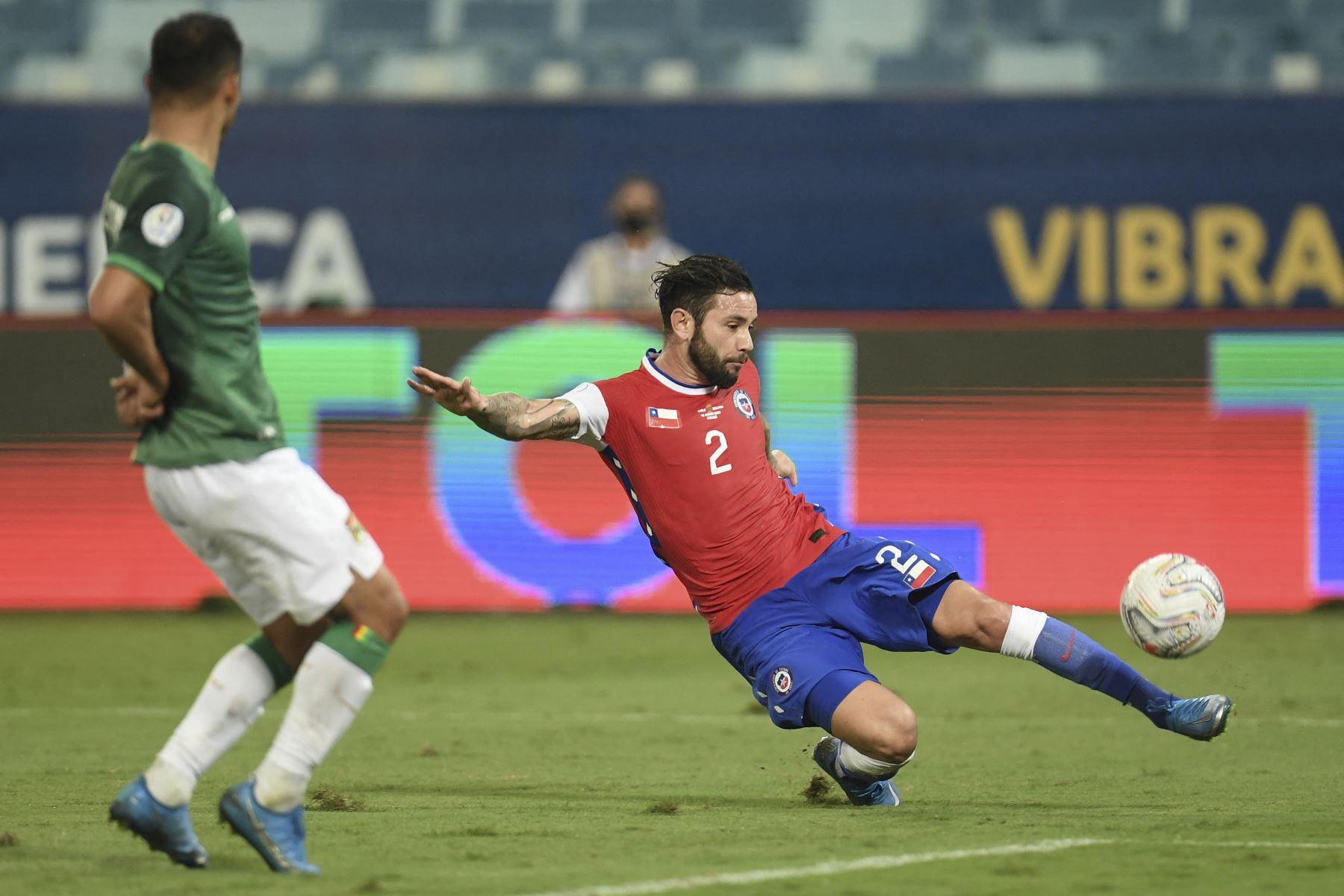 El chileno Eugenio Mena dispara el balón mientras el boliviano Diego Bejarano intenta bloquearlo durante partido de la fase de grupos de la Copa América, en el Pantanal Arena de Cuiabá, Brasil. Foto. AFP