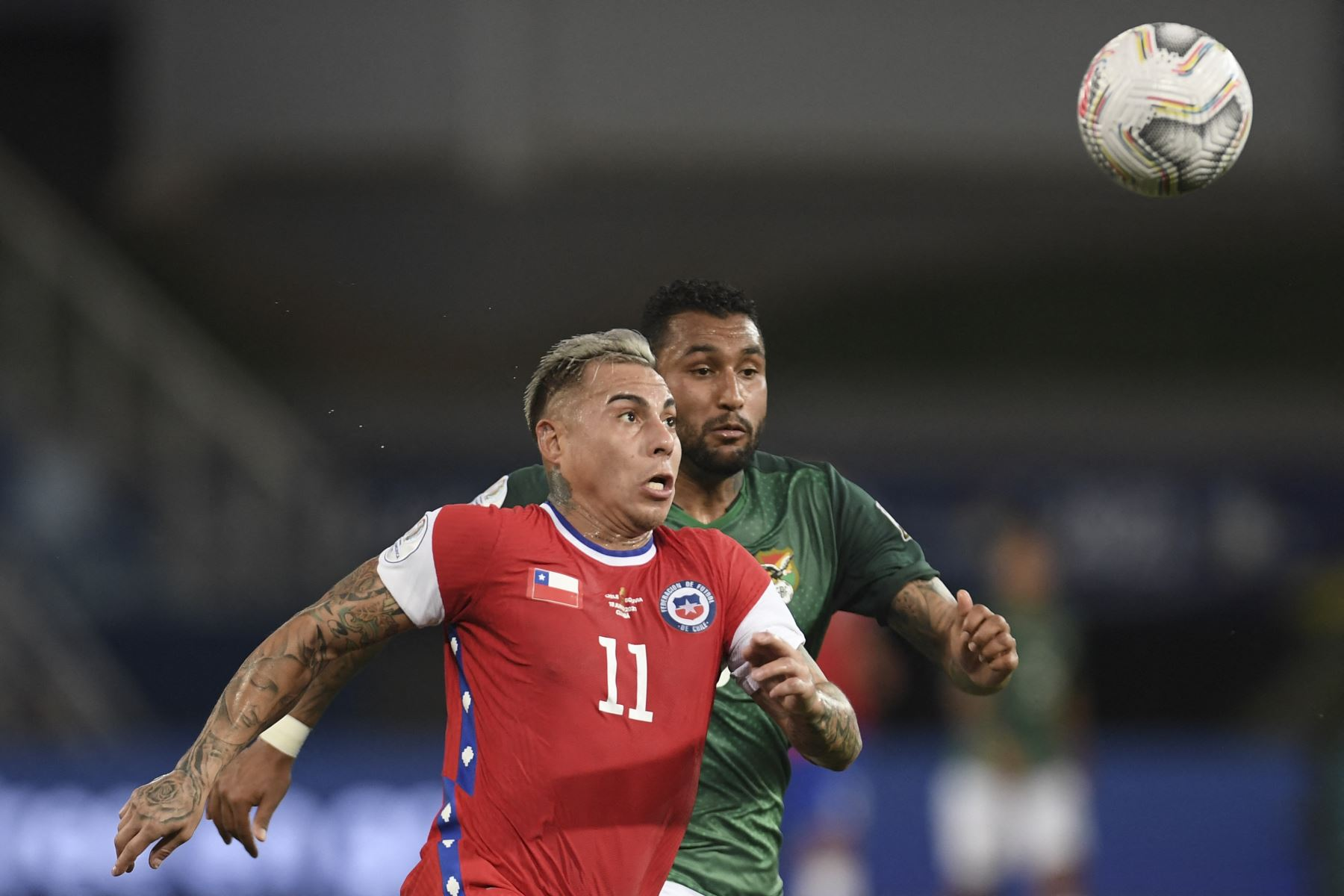 El chileno Eduardo Vargas y el boliviano Adrián Jusino compiten por el balón durante el partido de la fase de grupos de la Copa América, en el Pantanal Arena de Cuiabá, Brasil. Foto: AFP