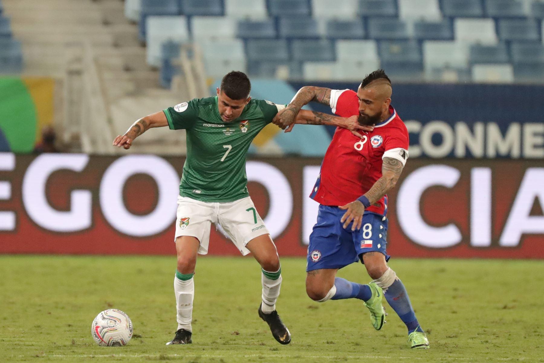 Arturo Vidal de Chile disputa el balón con Juan Carlos Arce de Bolivia durante un partido por el grupo A de la Copa América, en el estadio Arena Pantanal de Cuiabá, Brasil. Foto: EFE