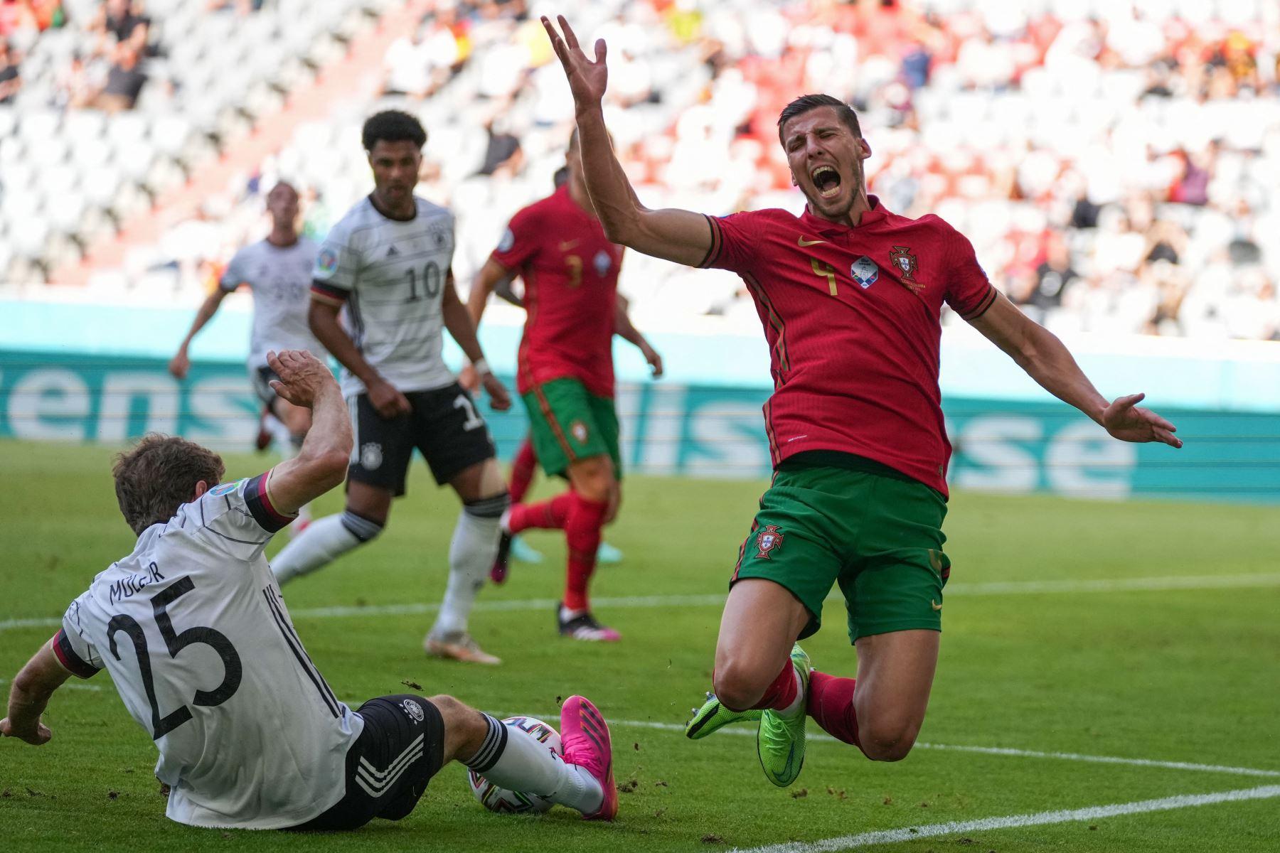 El defensor de Portugal Ruben Dias  cae en un desafío con el delantero alemán Thomas Mueller durante el partido de fútbol del Grupo F de la UEFA EURO 2020 entre Portugal y Alemania en el Allianz Arena de Múnich. Foto: AFP