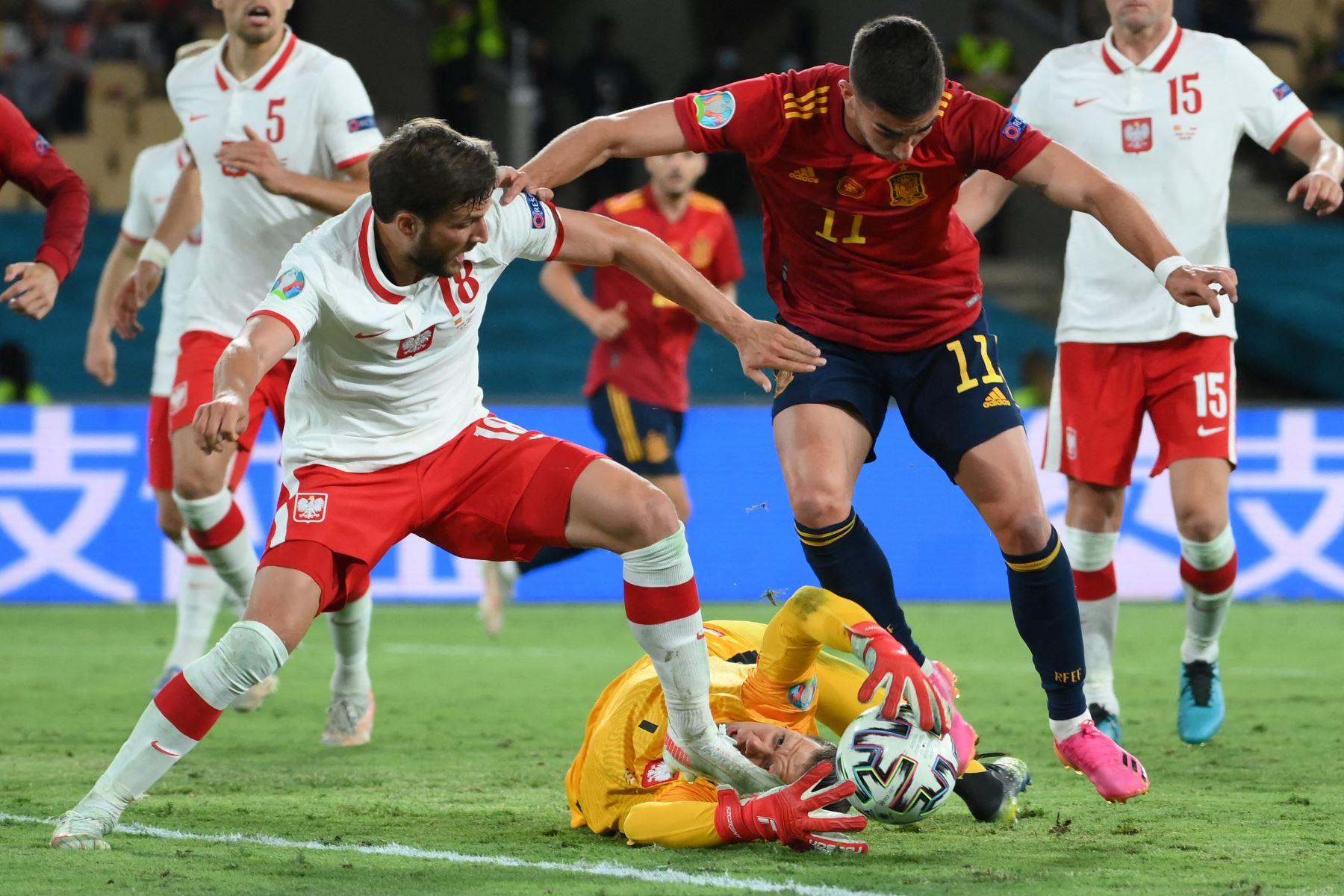 El portero polaco Wojciech Szczesny (C) intenta agarrar el balón mientras el defensor polaco Bartosz Bereszynski (L) desafía al mediocampista español Ferran Torres (R) durante el partido de fútbol del Grupo E de la UEFA EURO 2020 entre España y Polonia en el Estadio La Cartuja en Sevilla, España. Foto: AFP