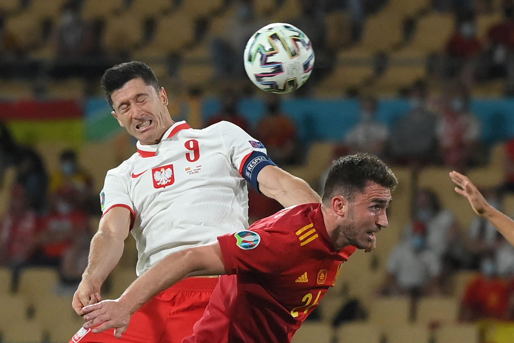 El delantero polaco Robert Lewandowski (L) cabecea el balón sobre el defensor español Aymeric Laporte para marcar el empate durante el partido de fútbol del Grupo E de la UEFA EURO 2020 entre España y Polonia en el Estadio La Cartuja en Sevilla, España. Foto: AFP