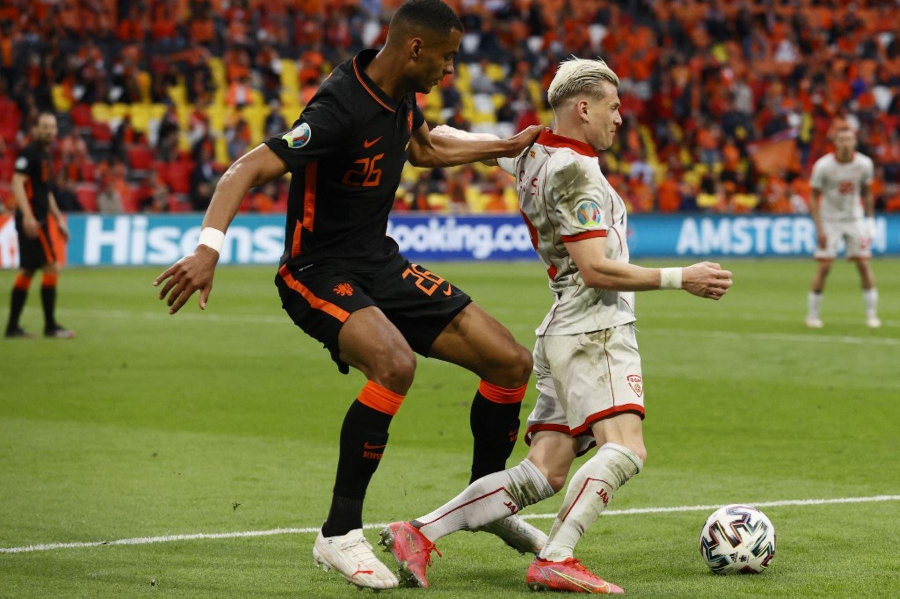 El delantero holandés Cody Gakpo (L) compite con el defensor de Macedonia del Norte Ezgjan Alioski durante el partido de fútbol del Grupo C de la UEFA EURO 2020 entre Macedonia del Norte y Holanda en el Johan Cruyff Arena de Ámsterdam el 21 de junio de 2021. Foto: AFP