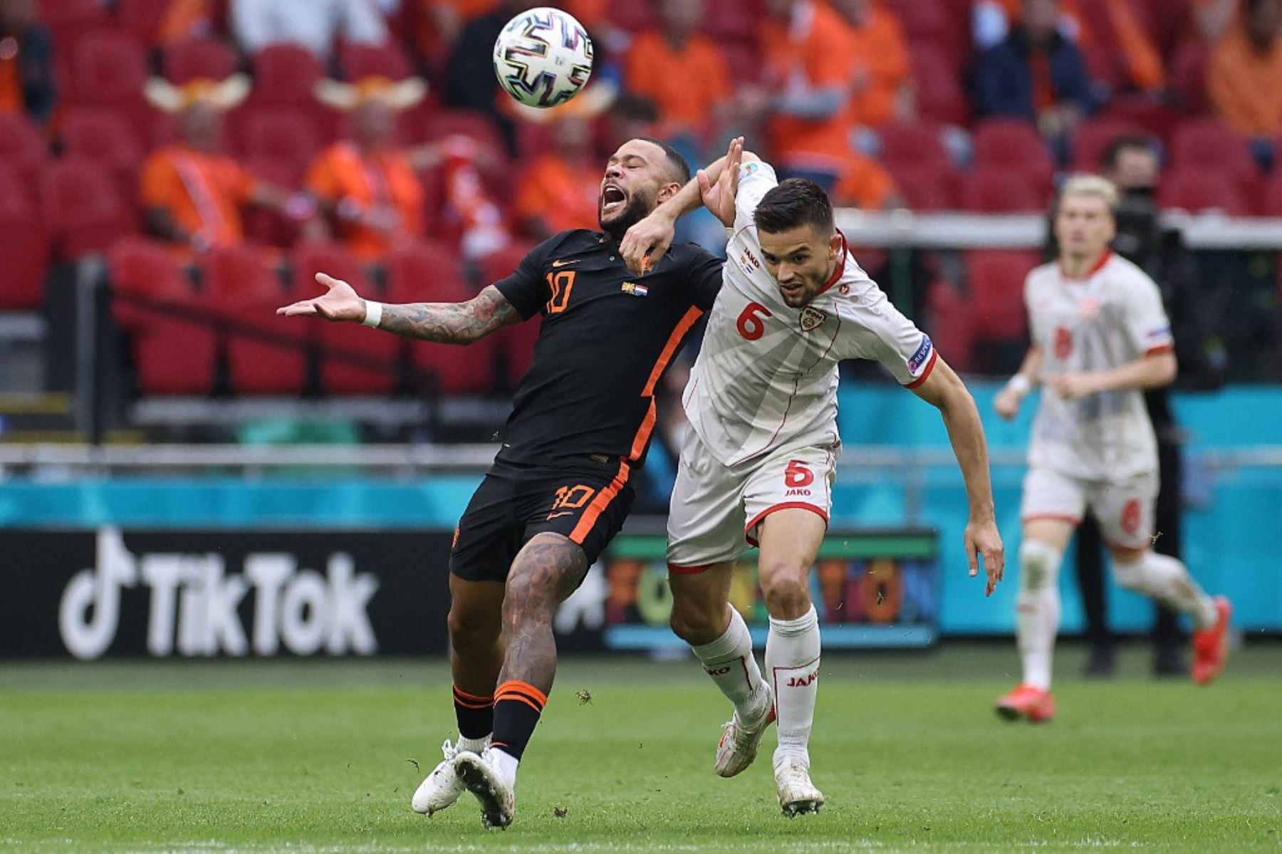 El delantero holandés Memphis Depay (L) compite con el defensor de Macedonia del Norte Visar Musliu durante el partido de fútbol del Grupo C de la UEFA EURO 2020 entre Macedonia del Norte y Holanda en el Johan Cruyff Arena en Ámsterdam el 21 de junio de 2021. Foto: AFP