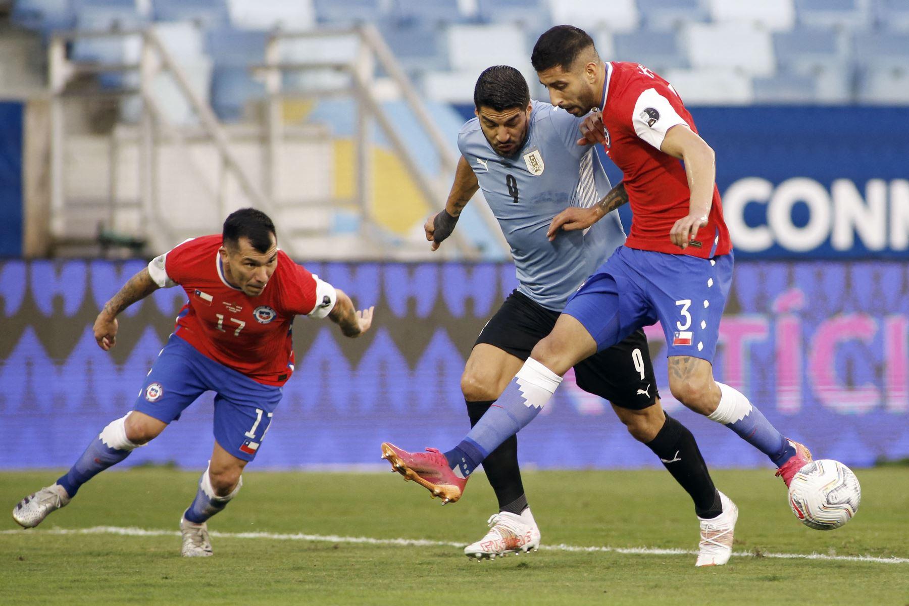 Los chilenos Gary Medel y Guillermo Maripan compiten por el balón con el uruguayo Luis Suárez  durante su partido de la fase de grupos del torneo de fútbol Conmebol Copa América 2021 en el Pantanal Arena de Cuiabá, Brasil. Foto: AFP