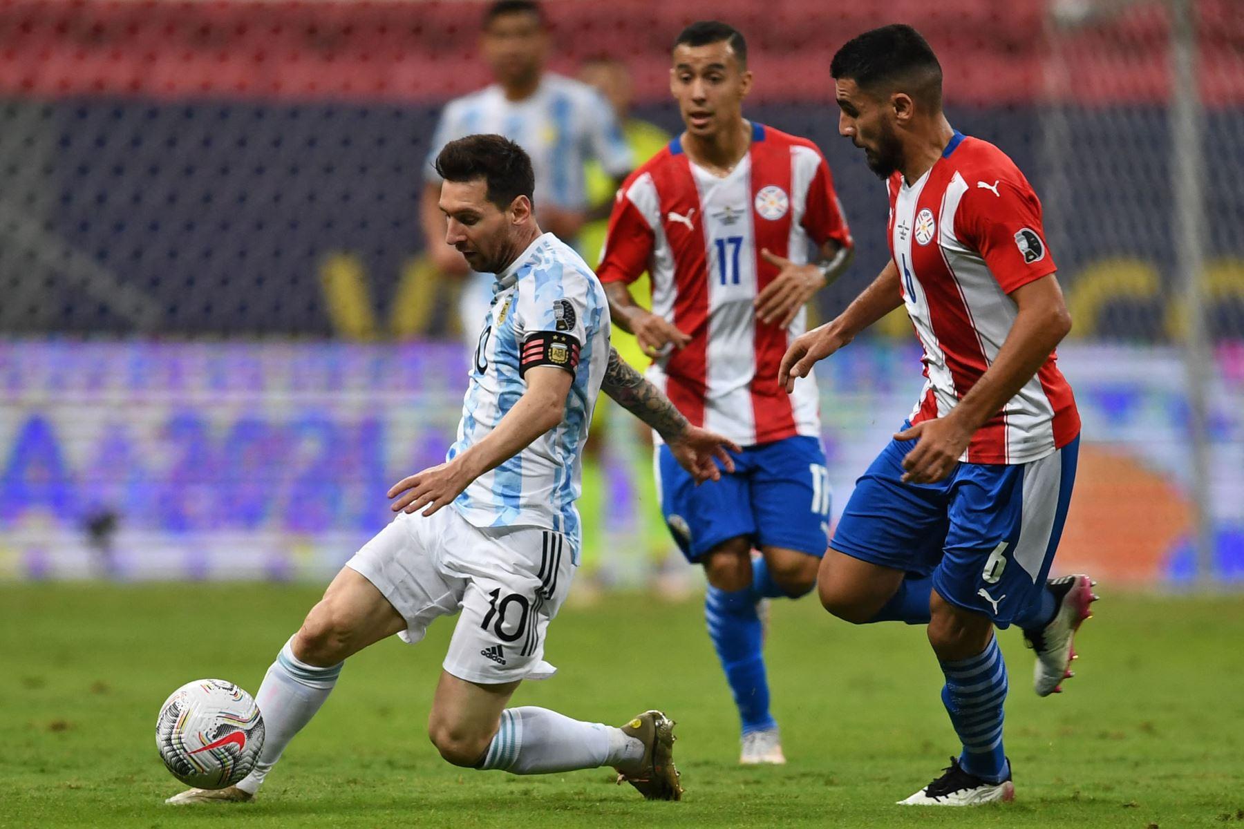 El argentino Lionel Messi  el paraguayo Junior Alonso compiten por el balón durante el partido de la fase de grupos del torneo de fútbol Conmebol Copa América 2021 en el estadio Mane Garrincha de Brasilia. Foto: AFP