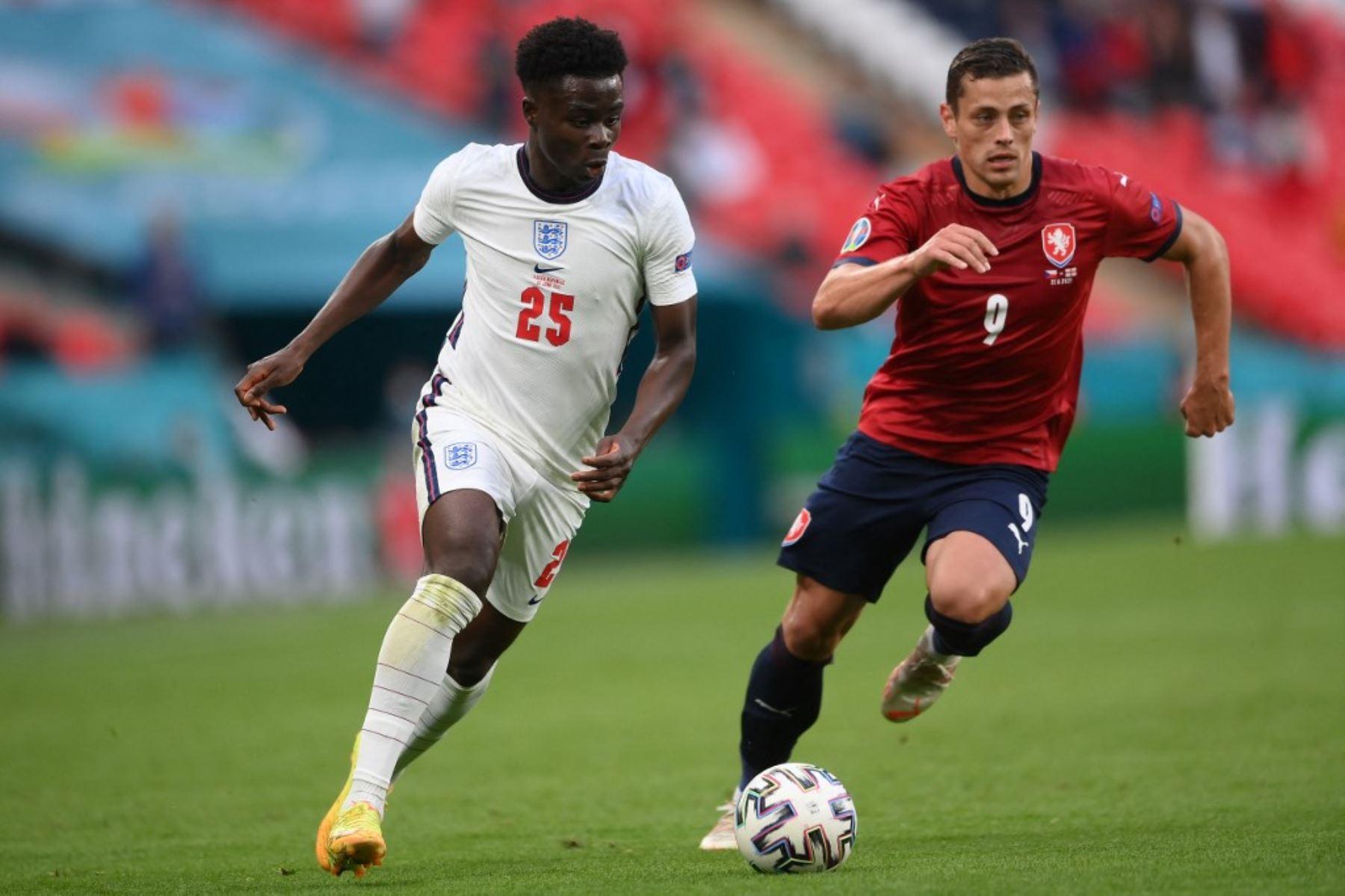 El centrocampista de Inglaterra Bukayo Saka (L) y el centrocampista de la República Checa Tomas Holes compiten por el balón durante el partido de fútbol del Grupo D de la UEFA EURO 2020 entre la República Checa e Inglaterra en el estadio de Wembley en Londres el 22 de junio de 2021. Foto: AFP
