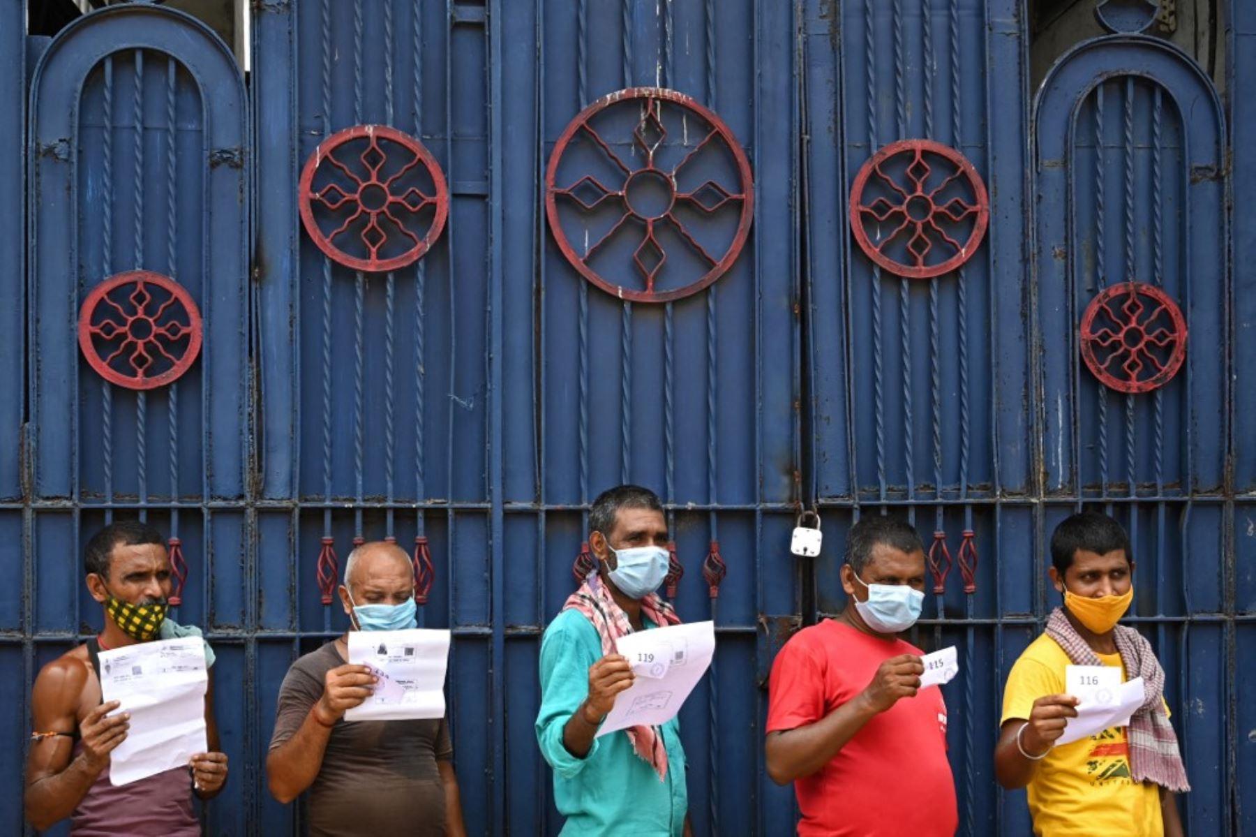 Los trabajadores sostienen documentos mientras esperan su turno para recibir la primera dosis de la vacuna Covishield contra el coronavirus Covid-19 en un autobús de pasajeros convertido en un centro de vacunación móvil en un mercado mayorista en Calcuta. Foto: AFP