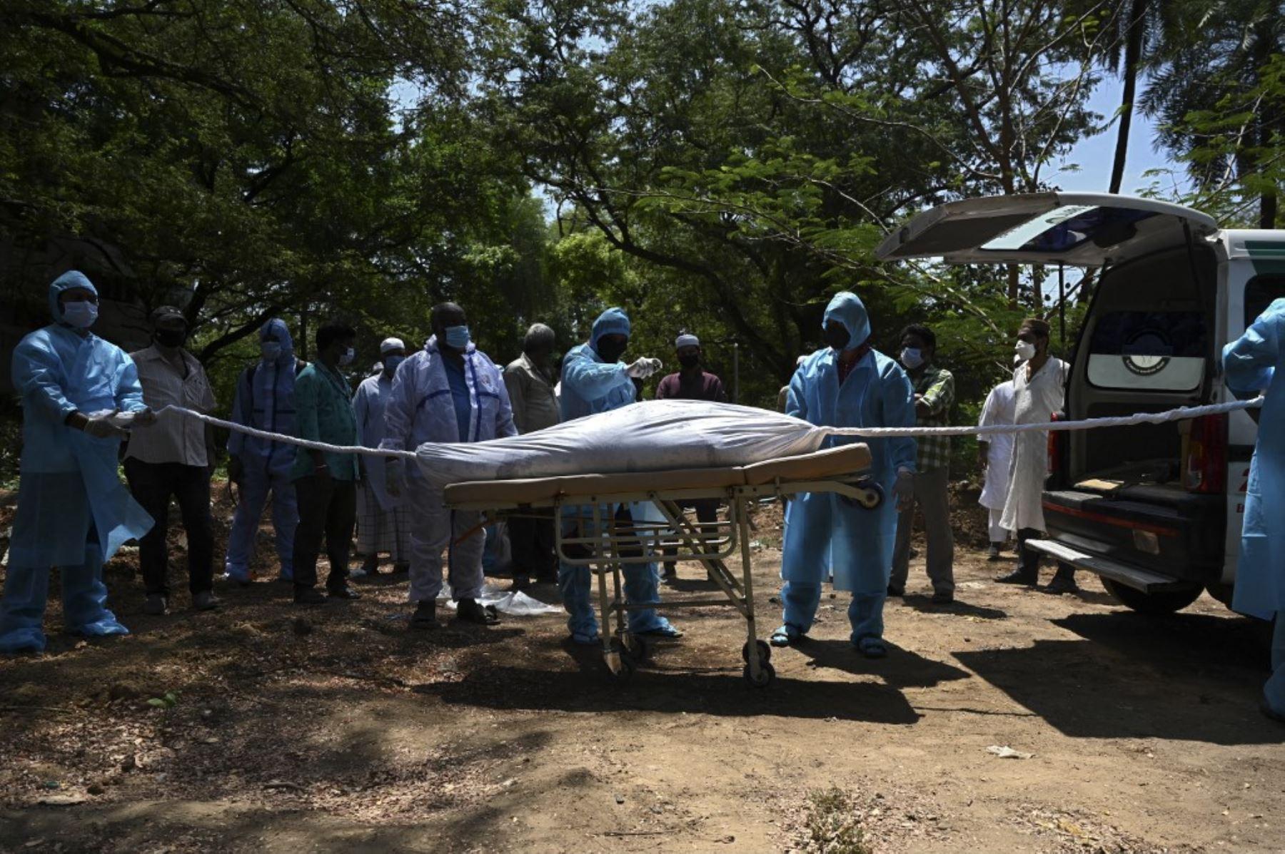 Voluntarios con equipo de protección se preparan para enterrar el cuerpo de una víctima del coronavirus Covid-19 en un cementerio en Chennai. Foto: AFP