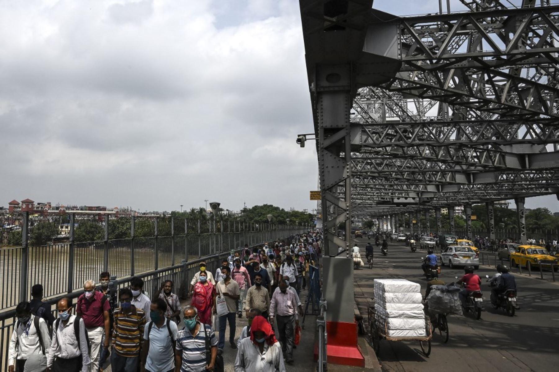 Los viajeros caminan mientras cruzan el puente Howrah mientras el gobierno estatal suspendió el transporte público regular durante un bloqueo impuesto para frenar la propagación del coronavirus Covid-19, en Calcuta. Foto: AFP
