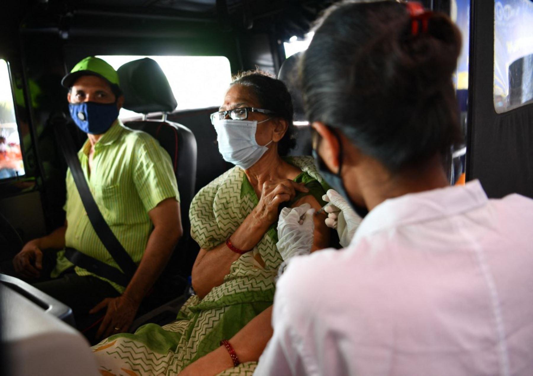 Un trabajador de salud inocula a una mujer con una dosis de una vacuna contra el coronavirus Covid-19, en un centro de vacunación dentro de un centro comercial en Mumbai. Foto: AFP