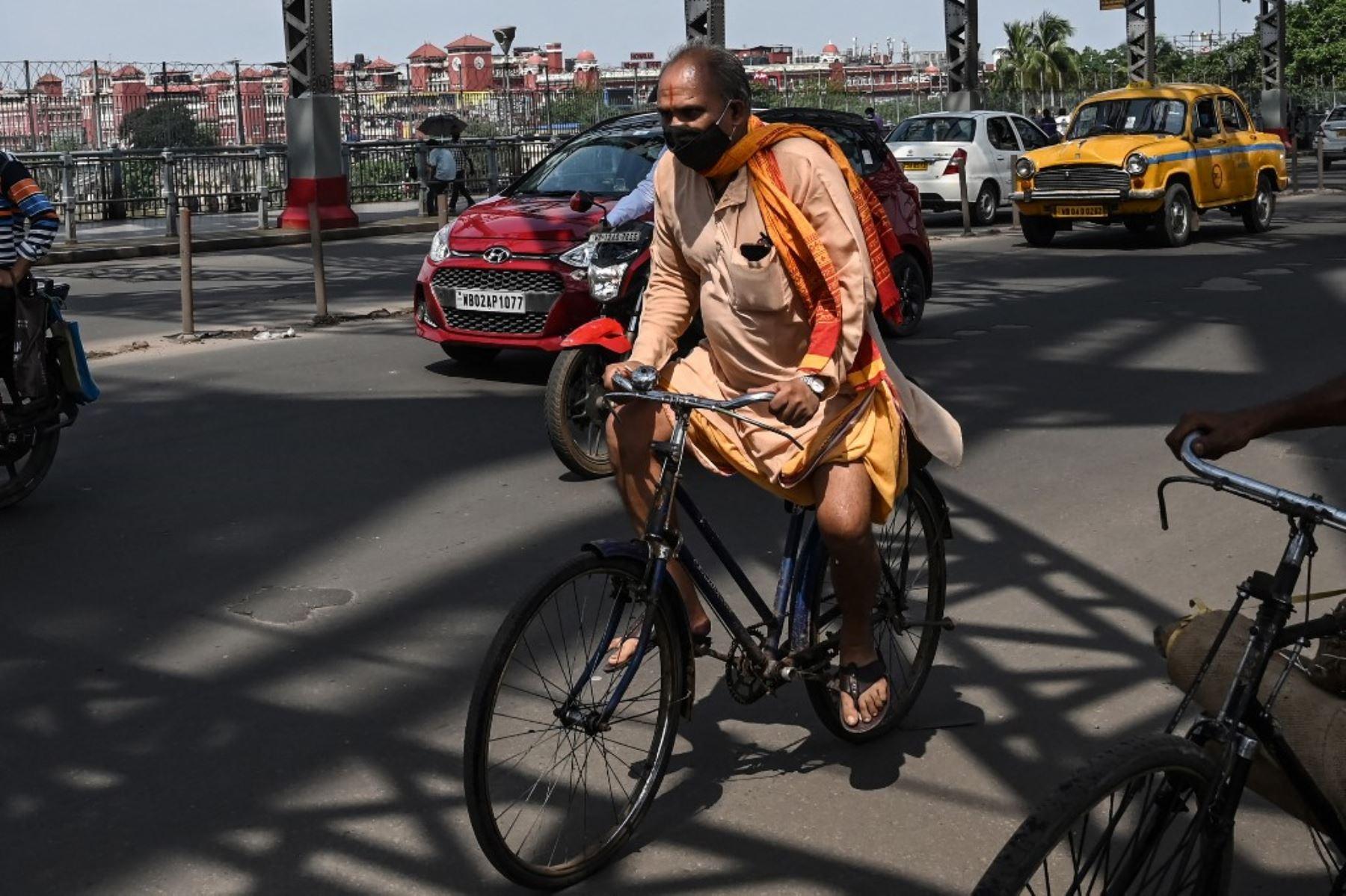 Un hombre cruza el puente Howrah en su bicicleta mientras el gobierno estatal suspendió el transporte público regular durante un bloqueo impuesto para frenar la propagación del coronavirus Covid-19, en Calcuta el 23 de junio de 2021. Foto: AFP