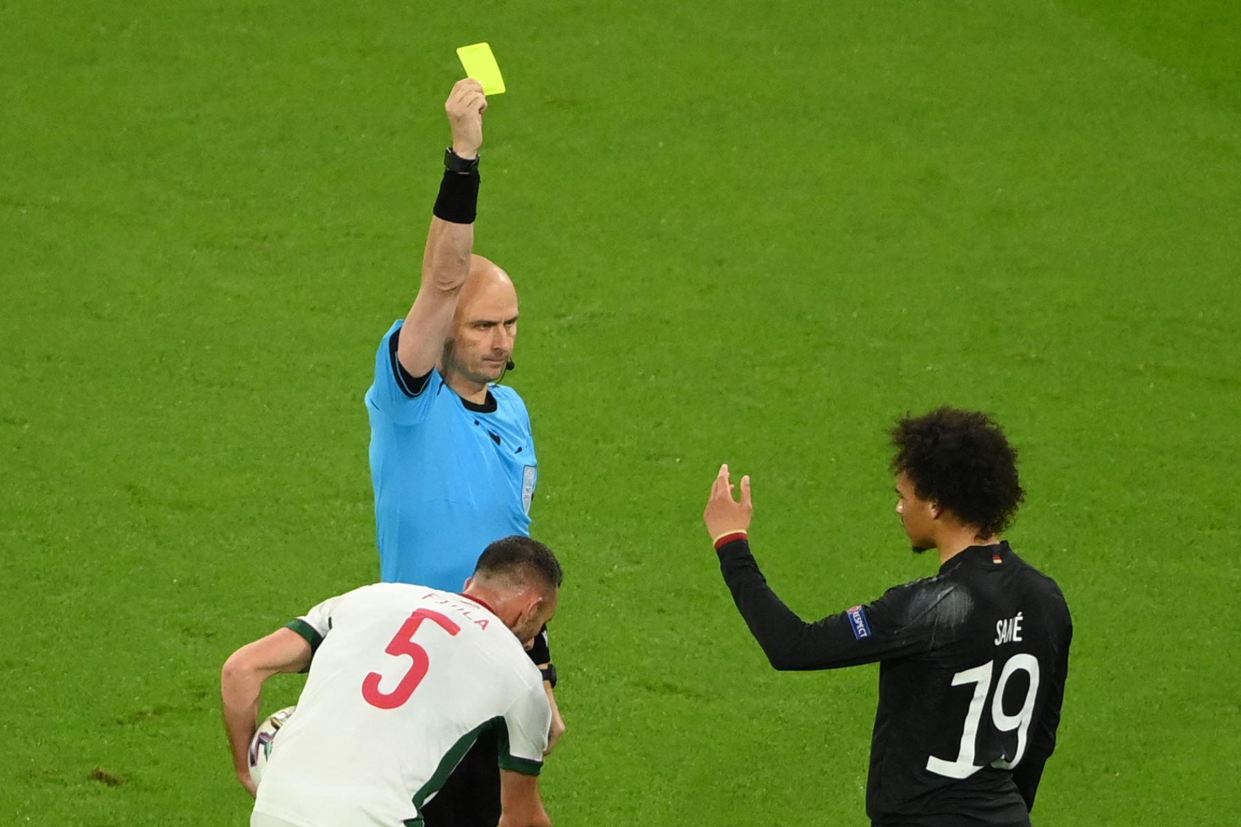 El árbitro ruso Sergei Karasev muestra una tarjeta amarilla al mediocampista alemán Leroy Sane por una falta durante el partido frente a Hungría por el Grupo F de la UEFA EURO 2020, en Múnich. Foto: AFP