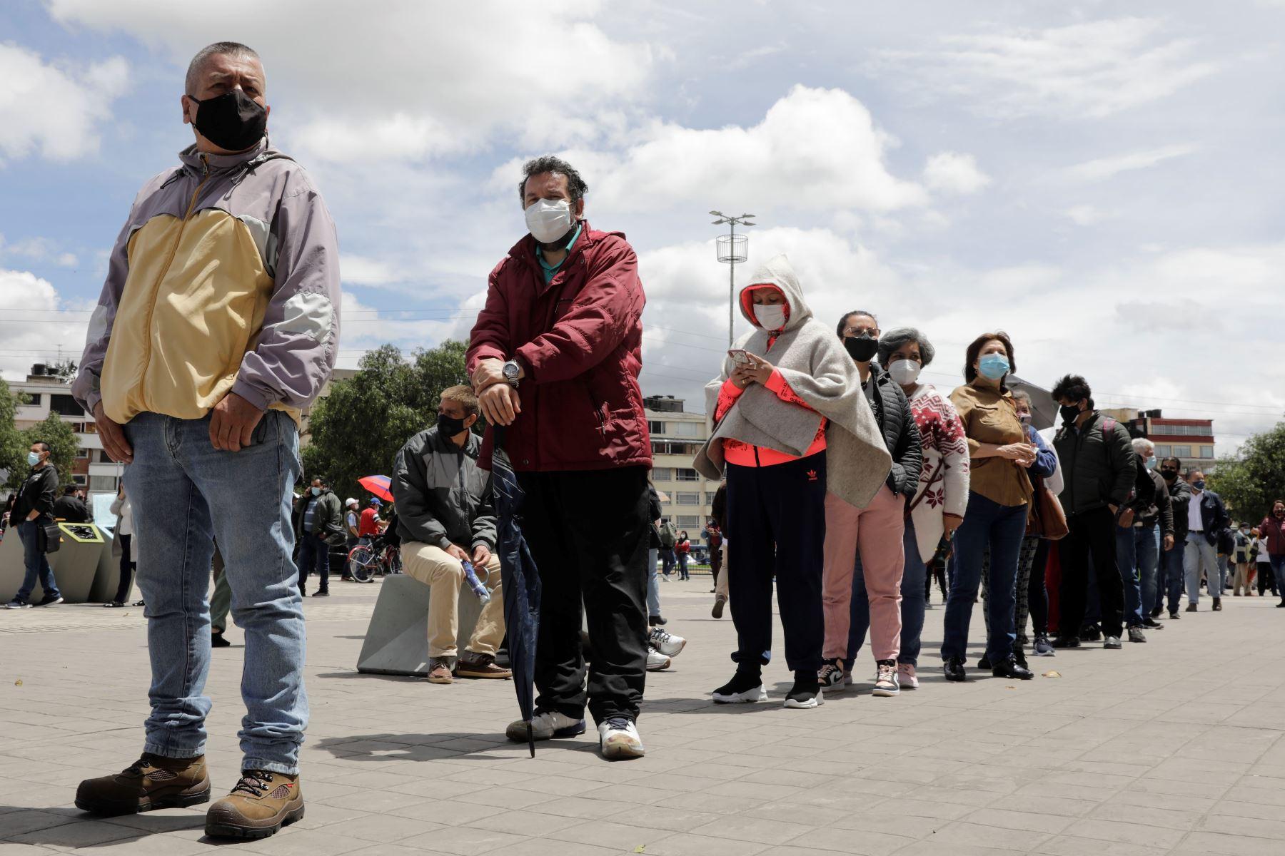 Decenas de personas hacen fila para vacunarse contra la covid-19 en Bogotá. Foto: EFE