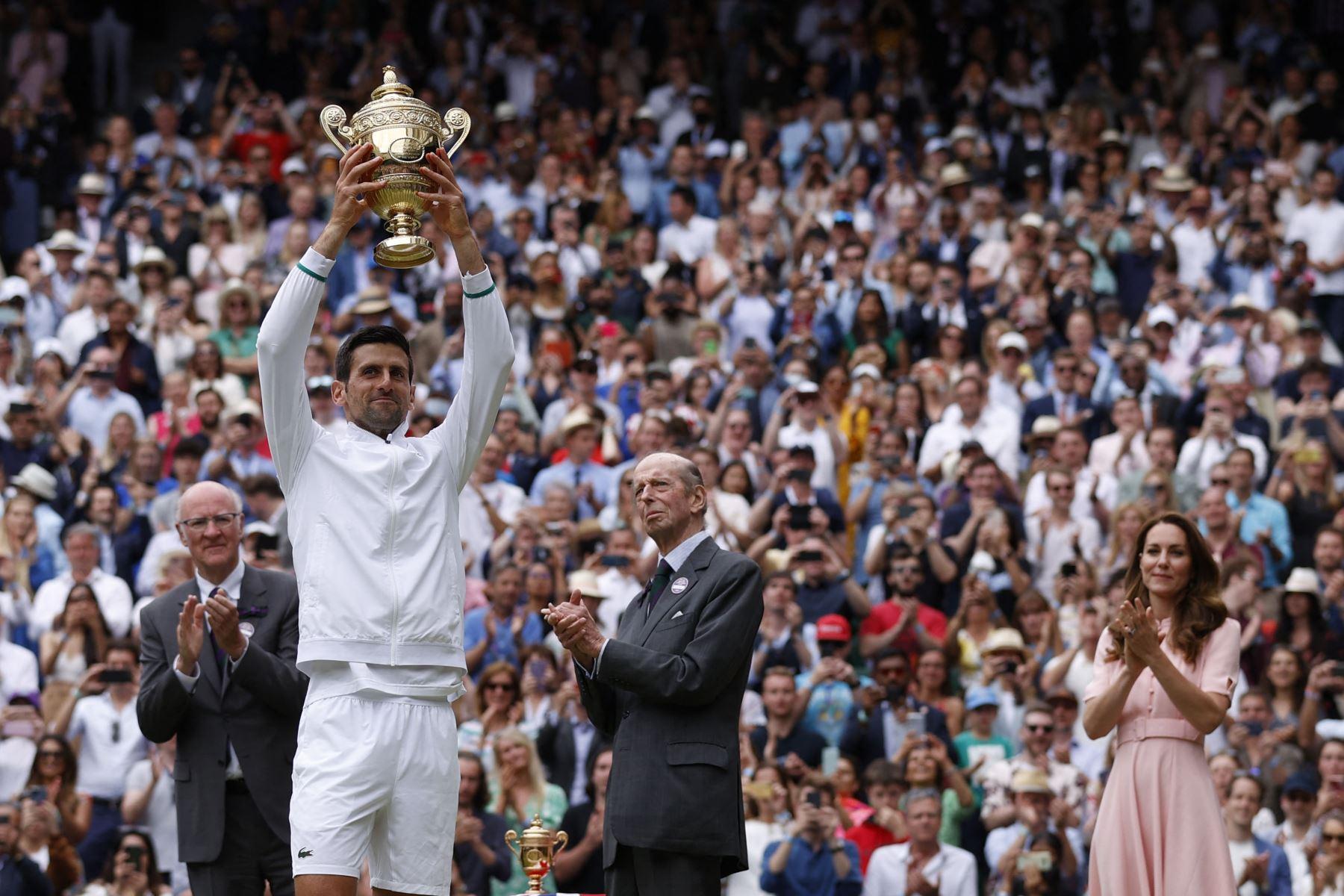 El serbio Novak Djokovic, con la británica Catherine , duquesa de Cambridge, sostiene el trofeo de ganador después de vencer al italiano Matteo Berrettini durante el partido final de individuales masculinos en el decimotercer día del Campeonato de Wimbledon 2021. Foto: AFP