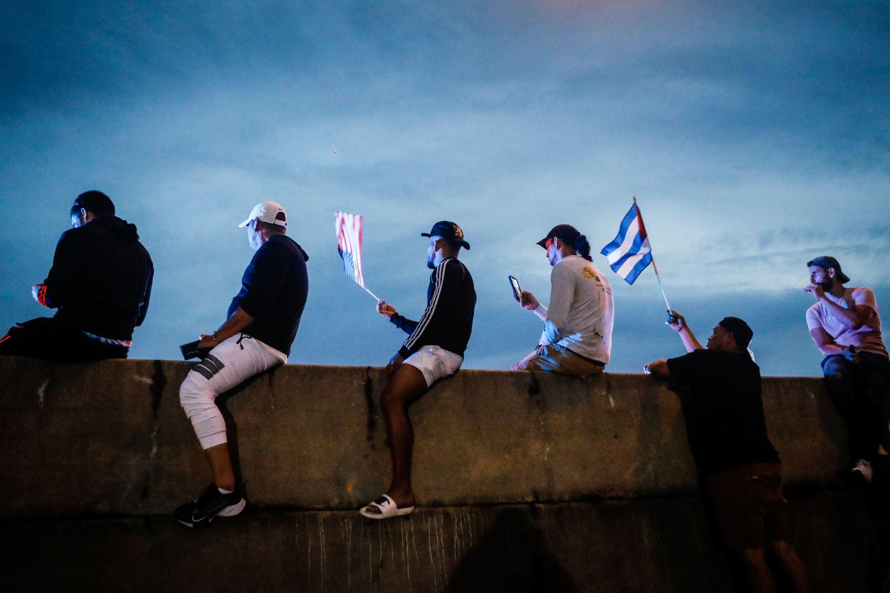 Personas sostienen banderas cubanas y estadounidenses mientras bloquean la Autopista Palmetto durante una protesta de apoyo a los cubanos que se manifiestan contra su gobierno, en Miami. Foto: AFP