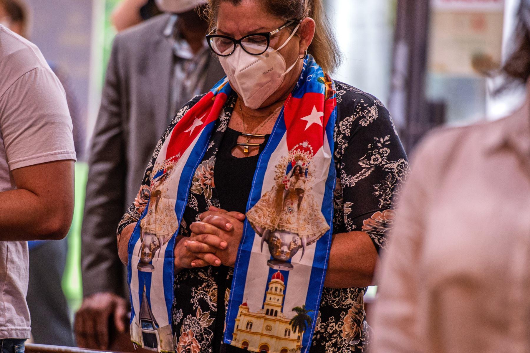 Una mujer reza durante una misa especial por Cuba ofrecida por el arzobispo de Miami, Thomas Wenski, hoy, en el Santuario Nacional Ermita de la Caridad, en Miami, Florida