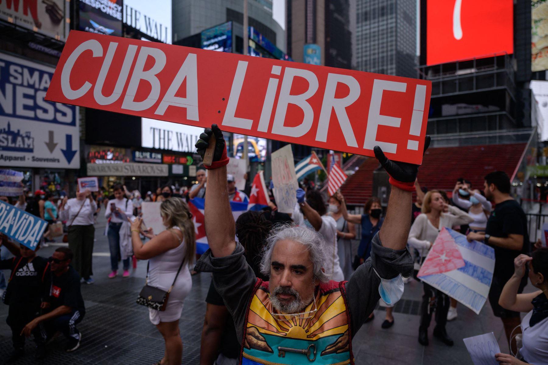 Los manifestantes sostienen pancartas durante una manifestación de solidaridad con las protestas antigubernamentales en Cuba, en Times Square, Nueva York. Foto: AFP