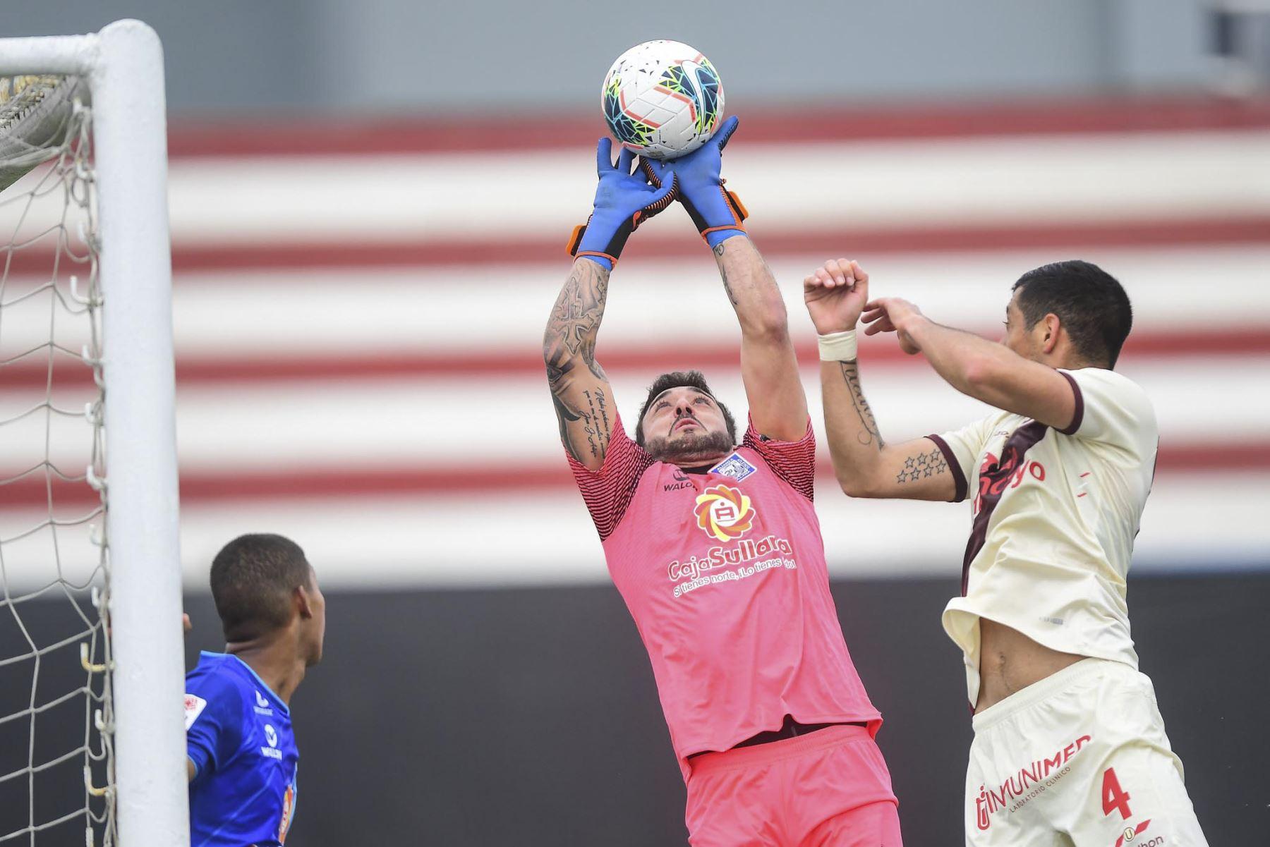 El portero I. Barrios de Alianza Atlético intenta controlar el remate de Universitario durante partido por la primera fecha de la Liga 1, en el Estadio Miguel Grau de Callao. Foto: Liga 1