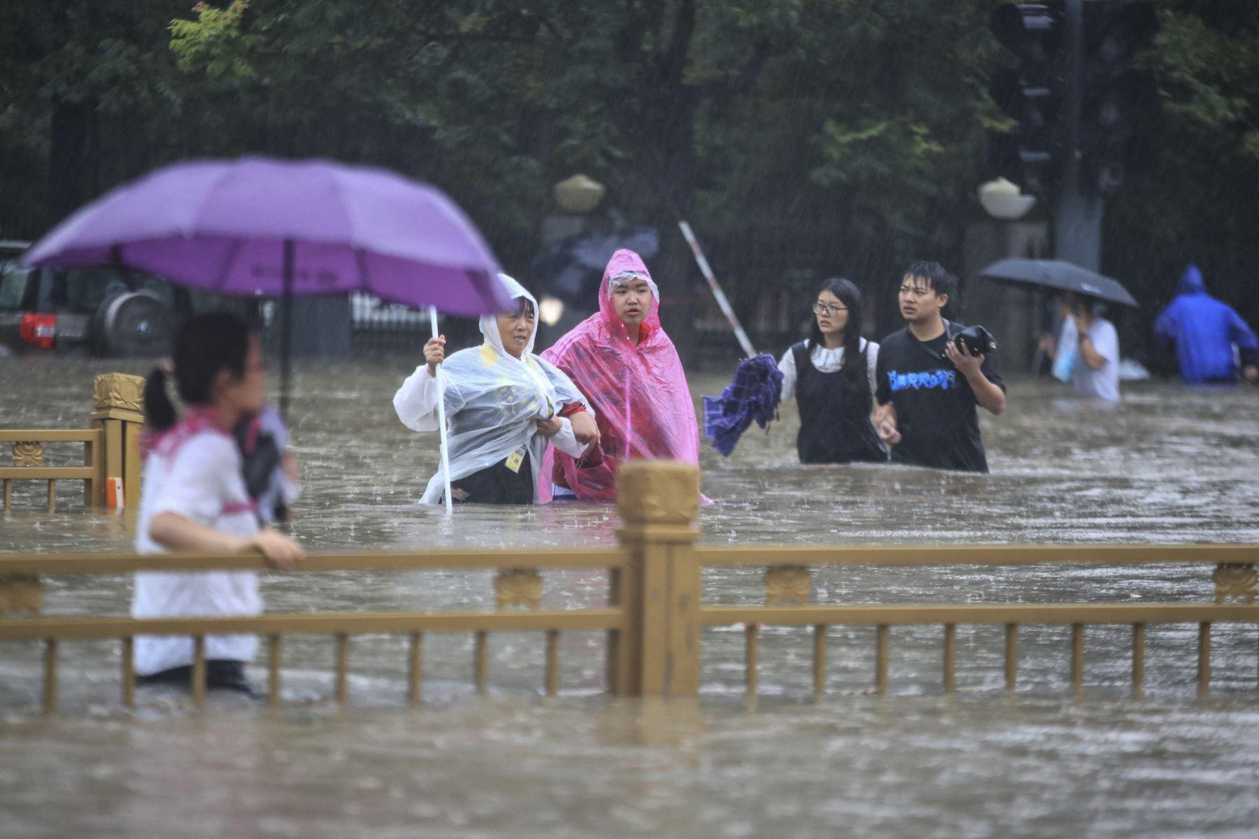 Un grupo de personas trata de cruzar una vía completamente inundada en Zhengzhou por las fuertes lluvias, en la provincia de Henan, en China. Foto: AFP