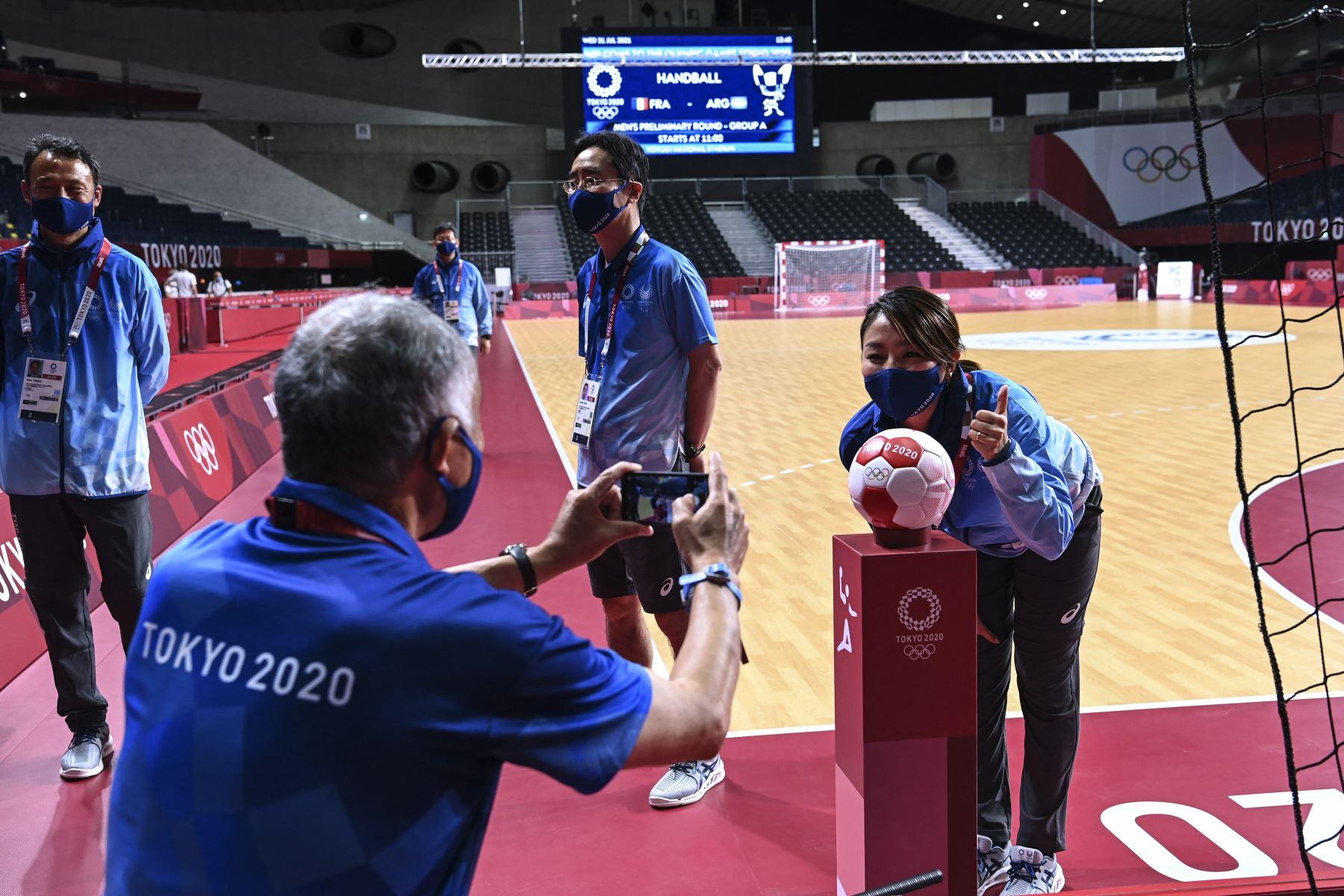 Los miembros del equipo olímpico se toman fotografías con el balón oficial de balonmano en el Estadio Nacional Yoyogi, sede del torneo de balonmano, en Tokio. Foto: AFP