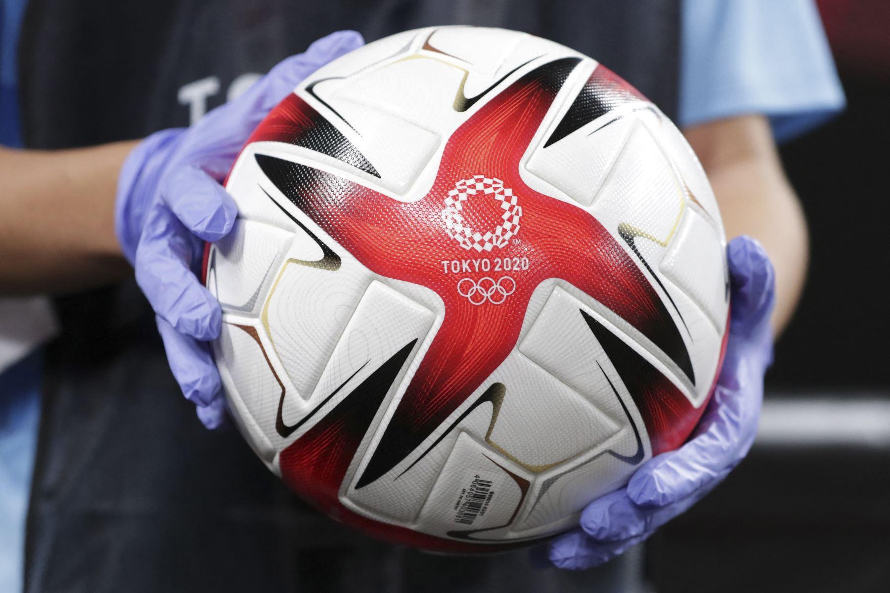 Una persona sostiene el balón de fútbol oficial antes del partido de fútbol de primera ronda del grupo E femenino de los Juegos Olímpicos de Tokio 2020, entre Gran Bretaña y Chile. Foto: AFP