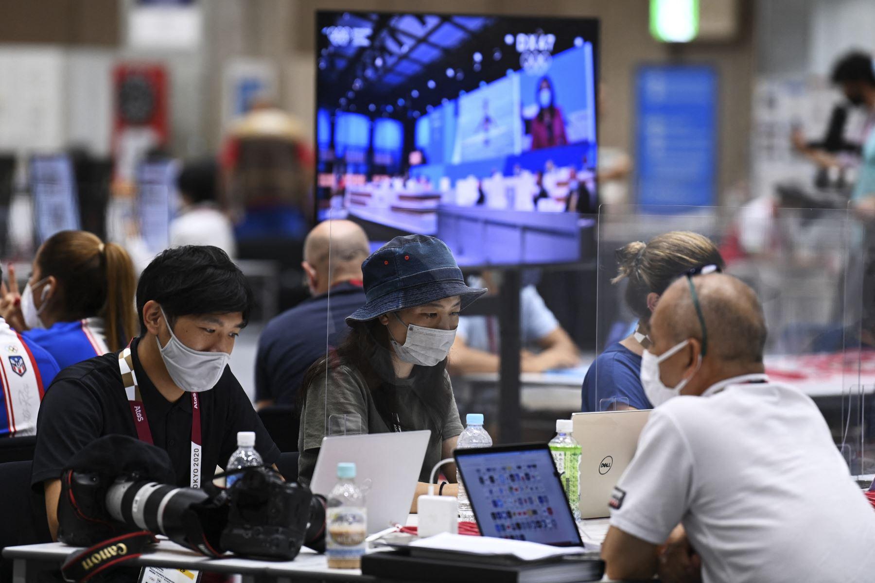 Periodistas con mascarillas como medida preventiva contra el coronavirus trabajan detrás del plexiglás protector, en el Centro de Prensa Principal, en Tokio. Foto: AFP