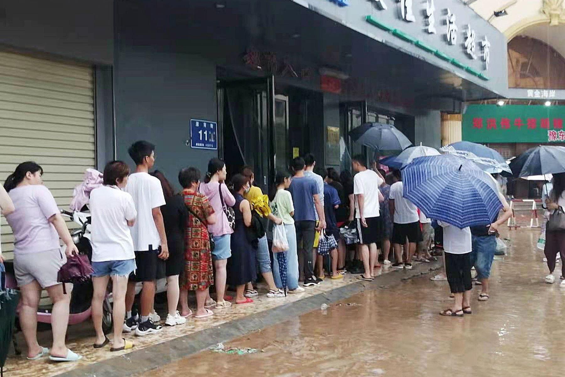 Personas hacen cola al lado de una pista inundada en medio de fuertes lluvias en Zhengzhou, provincia de Henan, China. Foto: EFE