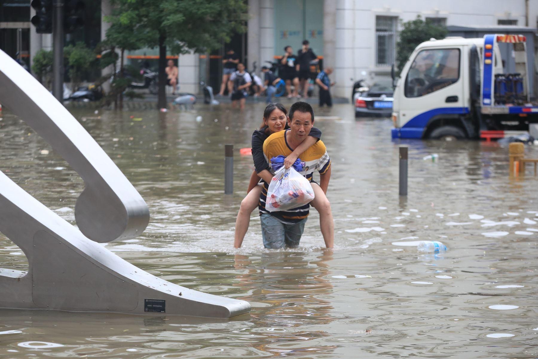 Un hombre carga a una mujer para cruzar la carretera  completamente inundada, en la ciudad de Zhengzhou, en la provincia de Henan, en el centro de China. Foto: EFE
