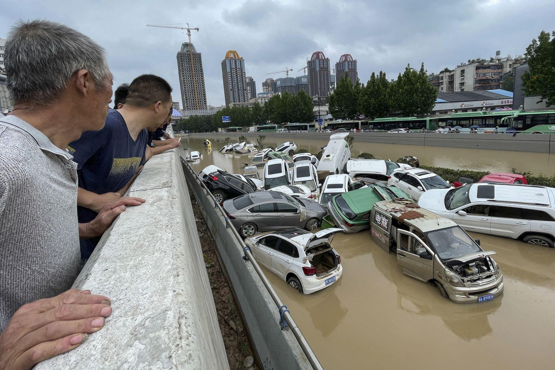 Personas observan los automóviles que quedaron sumergidos tras las fuertes lluvias en la ciudad de Zhengzhou, en la provincia central de Henan, en China. Foto: AFP