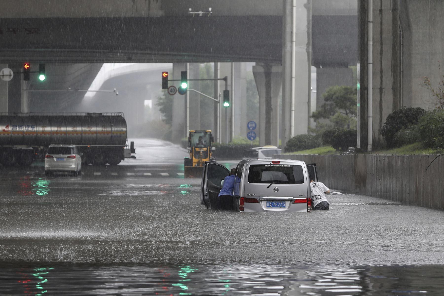 Personas tratan de empujar una camioneta atrapada tras las inundaciones por las fuertes lluvias en Zhengzhou, en la provincia de Henan, en China. Foto: AFP