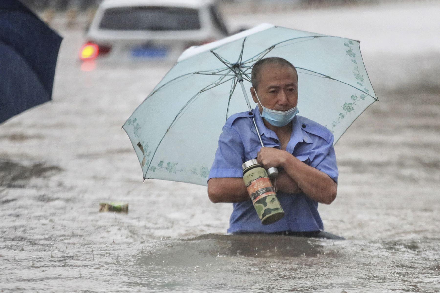Un hombre trata de cruzar una calle completamente inundada en Zhengzhou, en la provincia de Henan, en China. Foto: AFP