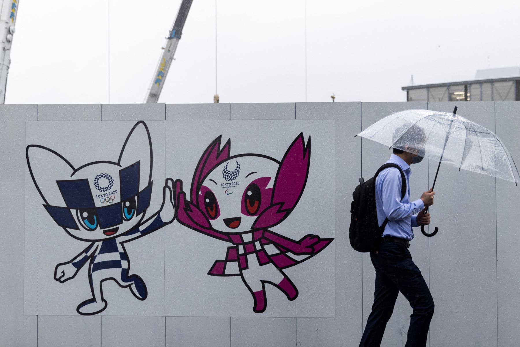 Un peatón pasa junto a un tablero de decoración de los Juegos Olímpicos y Paralímpicos de Tokio 2020 con ilustraciones de las mascotas de los Juegos Miraitowa (L) y Someity (R) en Tokio. Foto: AFP