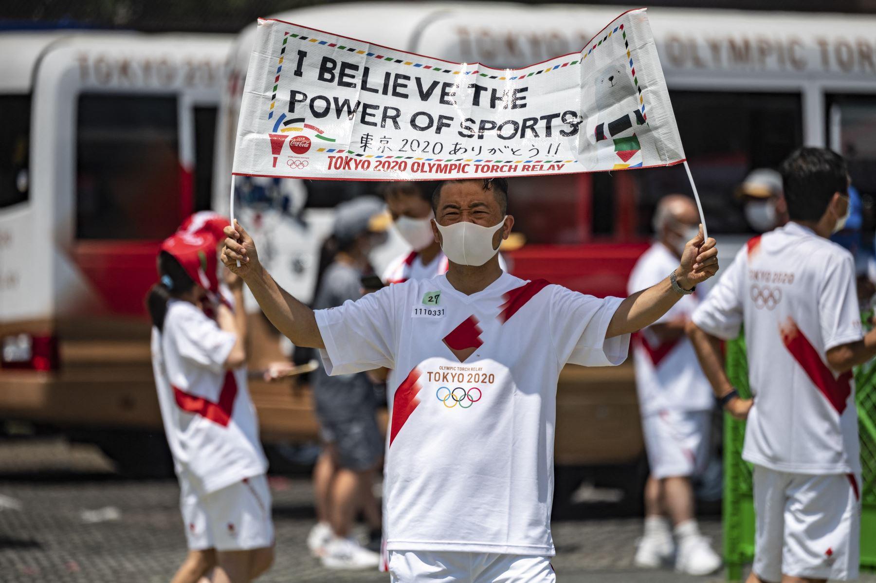 """El portador de la antorcha Akimasa Sano sostiene una pancarta que dice """"Creo en el poder de los deportes"""" durante la ceremonia de iluminación en el parque Hamacho en el distrito de Nihonbashi de Tokio. Foto: AFP"""