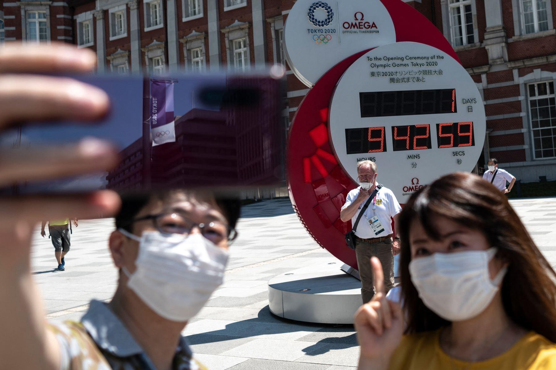 La gente toma fotografías del reloj de cuenta regresiva que indica 1 día y 9 horas antes del inicio de la ceremonia de apertura de los Juegos Olímpicos de Tokio 2020, en las afueras de la estación de Tokio. Foto: AFP