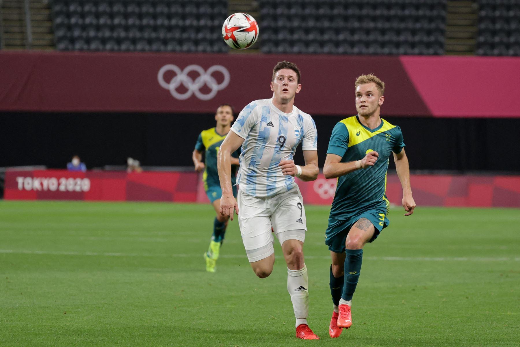 El delantero argentino Adolfo Gaich (C) compite por el balón con el defensor australiano Nathaniel Atkinson durante el partido de fútbol de primera ronda del grupo C masculino de los Juegos Olímpicos de Tokio 2020 entre Argentina y Australia en el Sapporo Dome. Foto: AFP