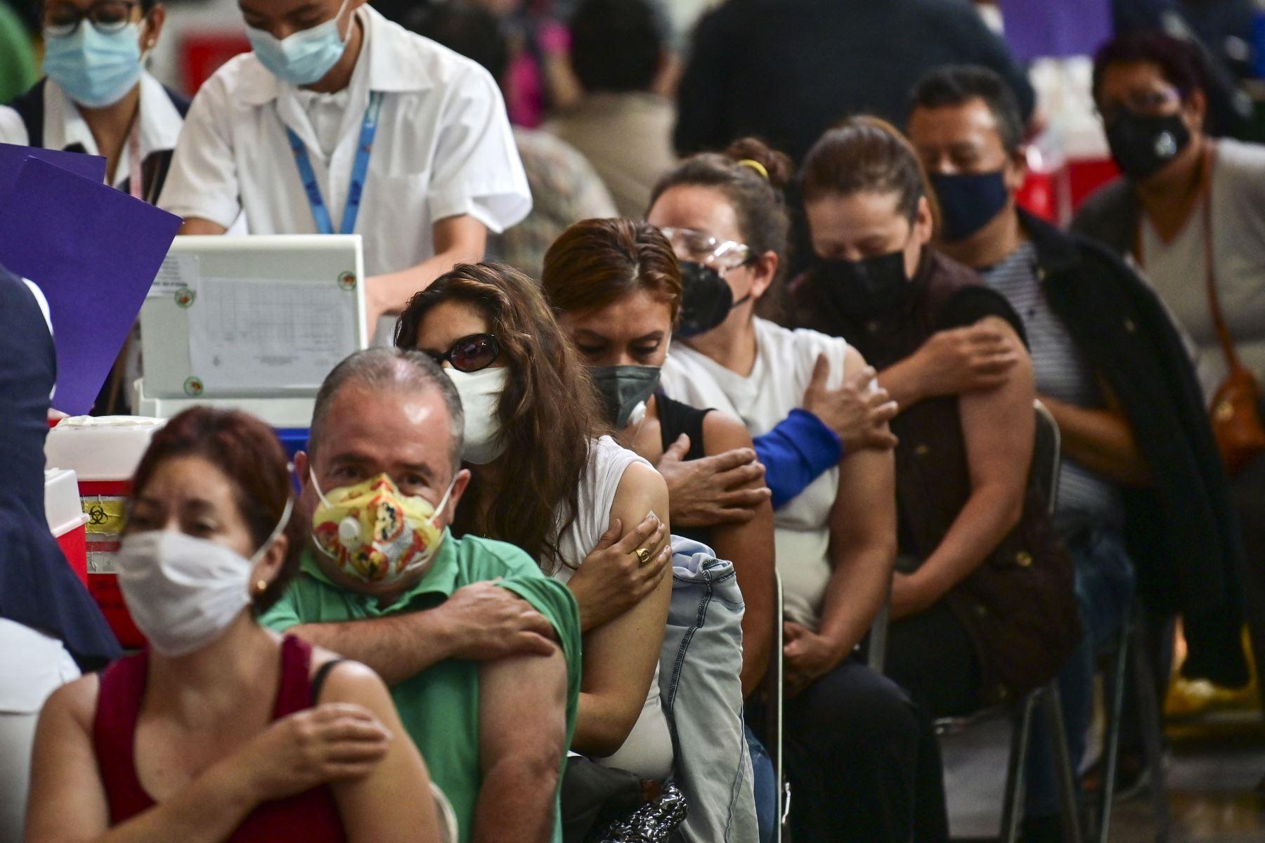 En esta foto, personas esperan luego de recibir dosis de la vacuna Pfizer-BioNTech contra COVID-19 en un centro de vacunación instalado en la Biblioteca Vasconcelos, en la Ciudad de México. Foto: AFP
